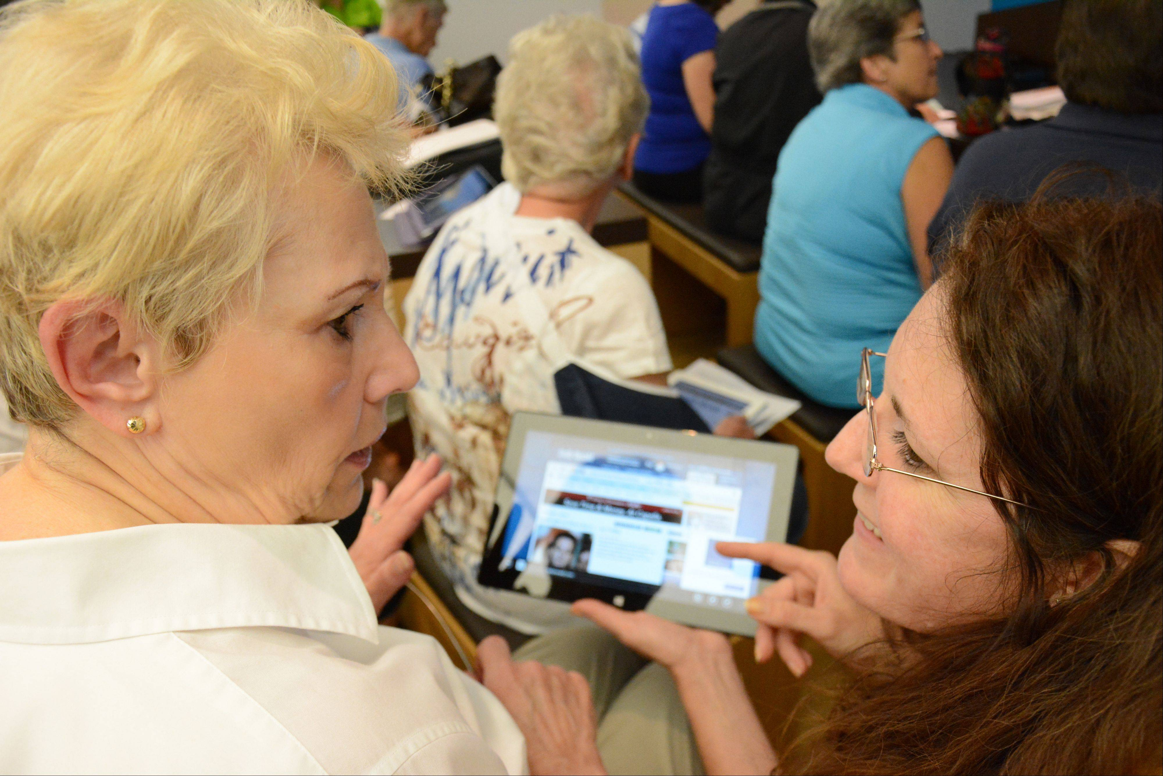 Barbara Corsi, left, of Mount Prospect, asks for help navigating the Daily Herald app from Rose May, Microsoft community development specialist.