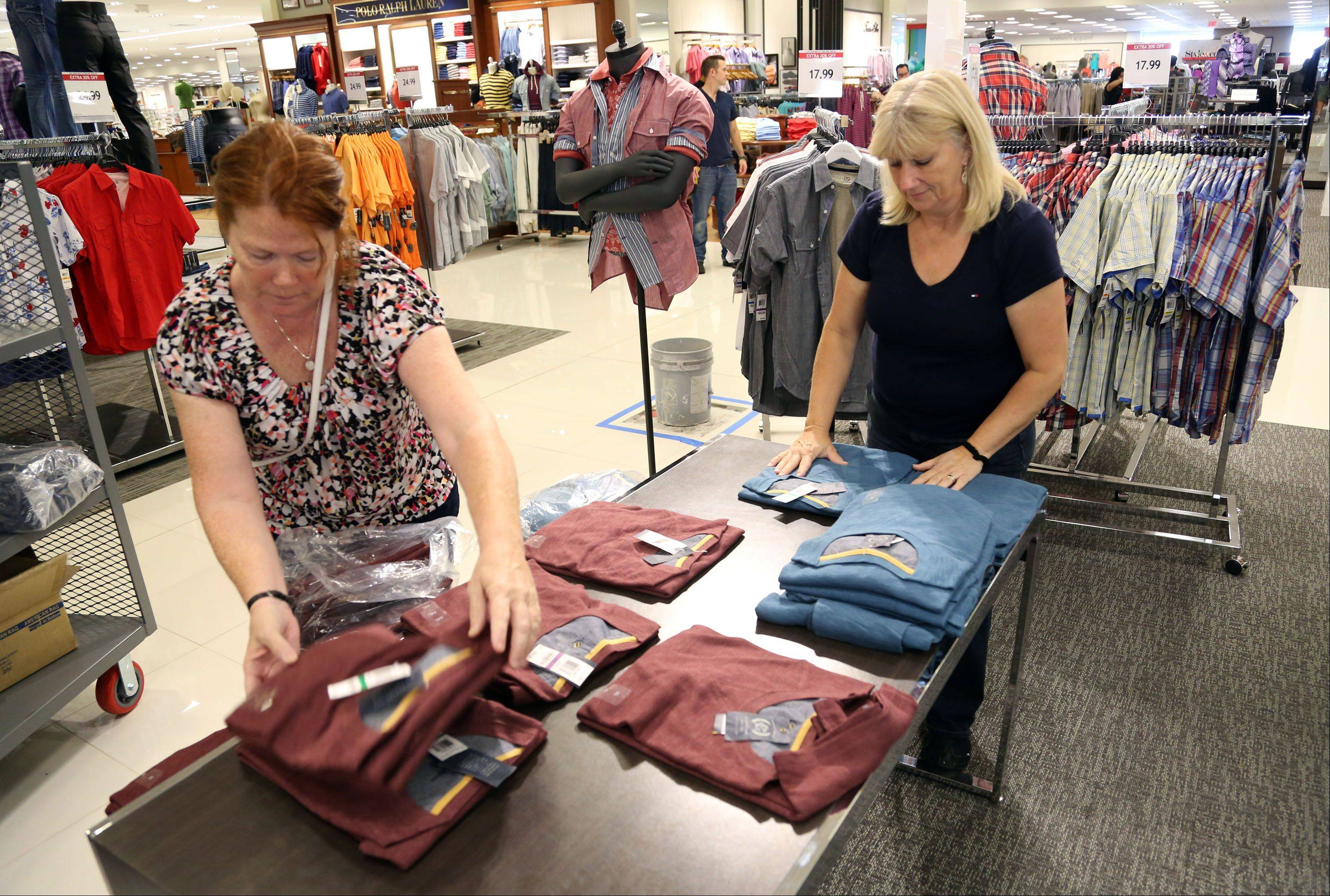 Macy's sales associates Madonna Stallings and Sue Cope sort through shirts as they prepare for a grand opening Wednesday at Gurnee Mills.