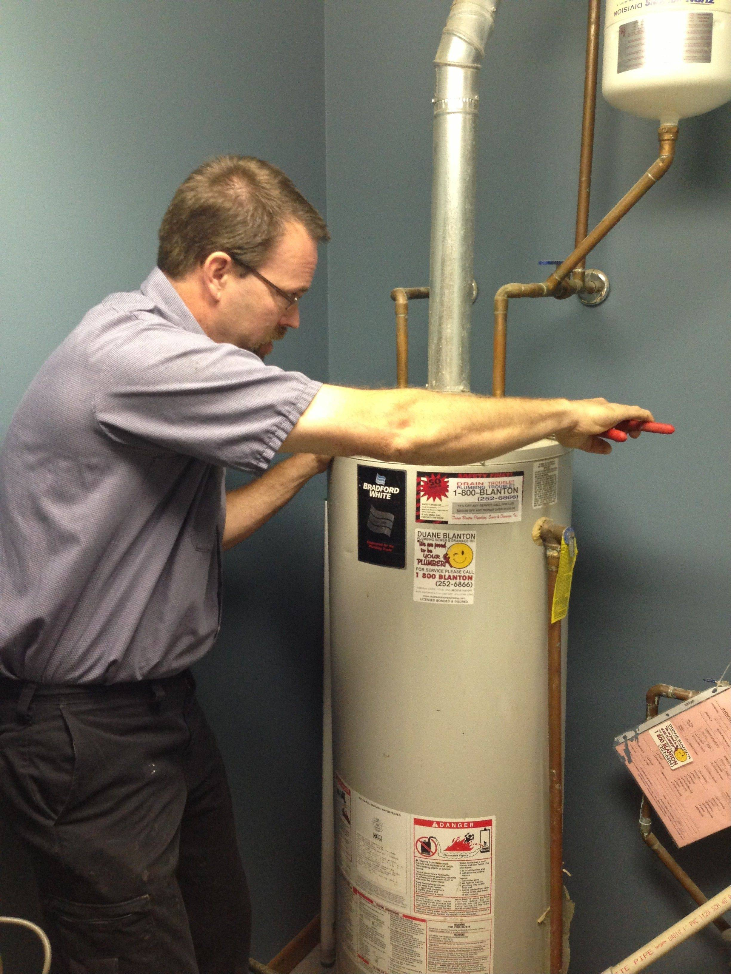 A plumber with Duane Blanton Plumbing installs a new water heater.