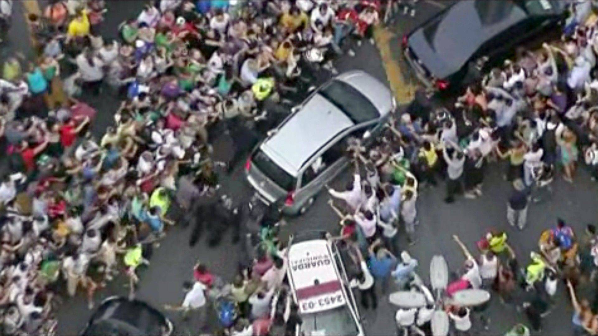 A crowd mobs the car carrying Pope Francis through Rio de Janeiro on Monday. Ecstatic believers forced the Fiat to stop several times as they swarmed around during the drive from the airport to an official opening ceremony in the center of the city.