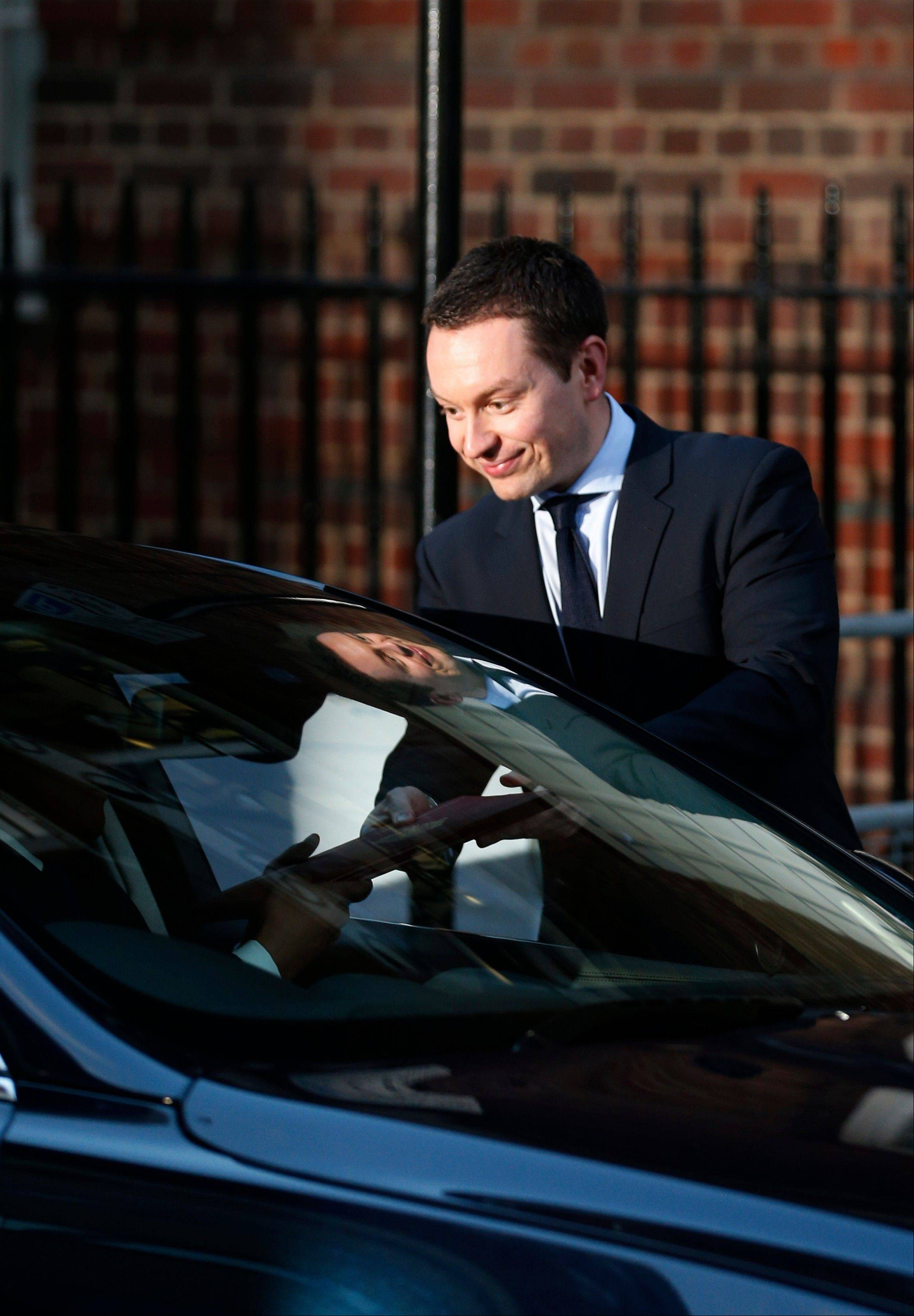 Ed Perkins, a Buckingham Palace official hands the birth announcement to colleague in a car to be driven to Buckingham Palace, outside St. Mary's Hospital exclusive Lindo Wing in London, Monday, July 22, 2013.