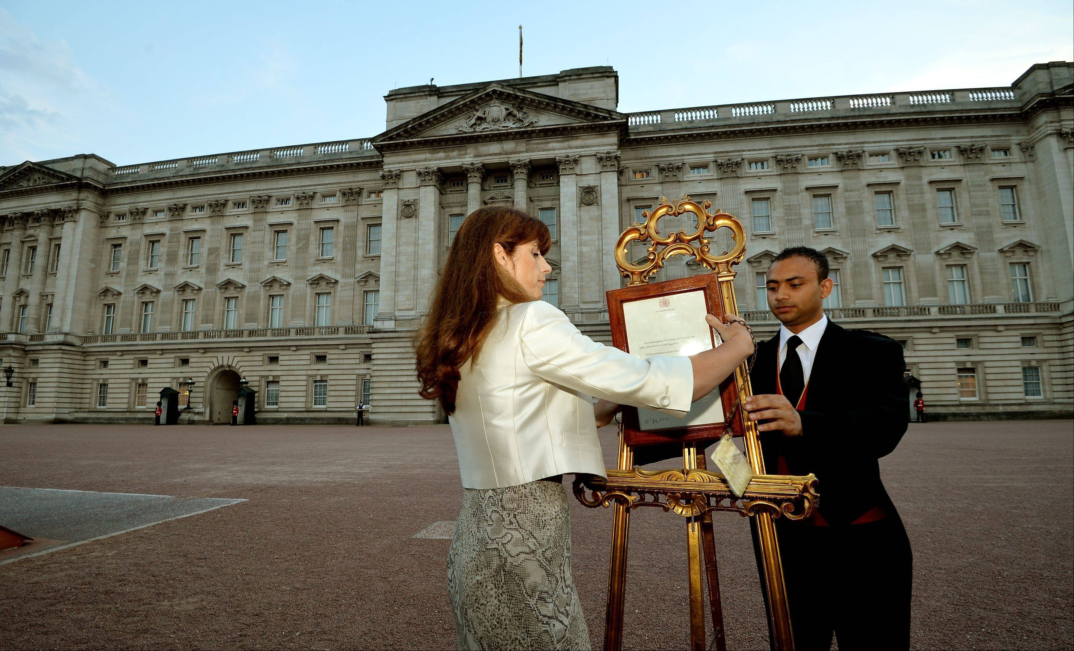 The Queen's Press Secretary Ailsa Anderson with Badar Azim, a footman, places an official document to announce the birth of a baby boy, at 4.24pm to the William and Kate, the Duke and Duchess of Cambridge at St Mary's Hospital, in the forecourt of Buckingham Palace in London Monday July 22, 2013.