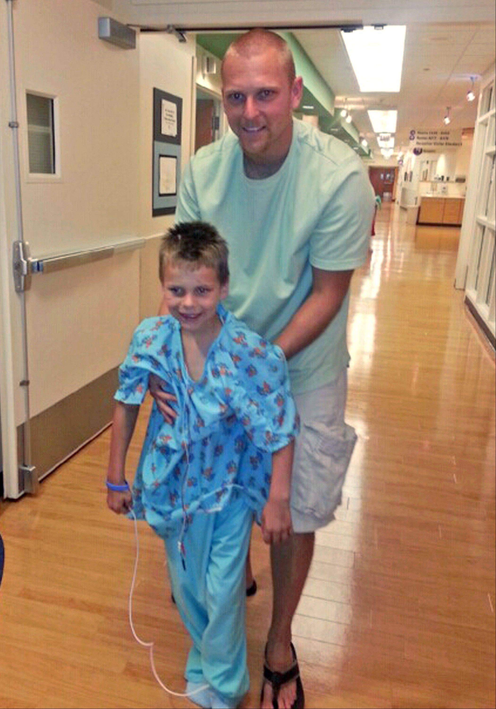 Nathan Woessner walks with his father, Greg, at Comer Children's Hospital in Chicago.