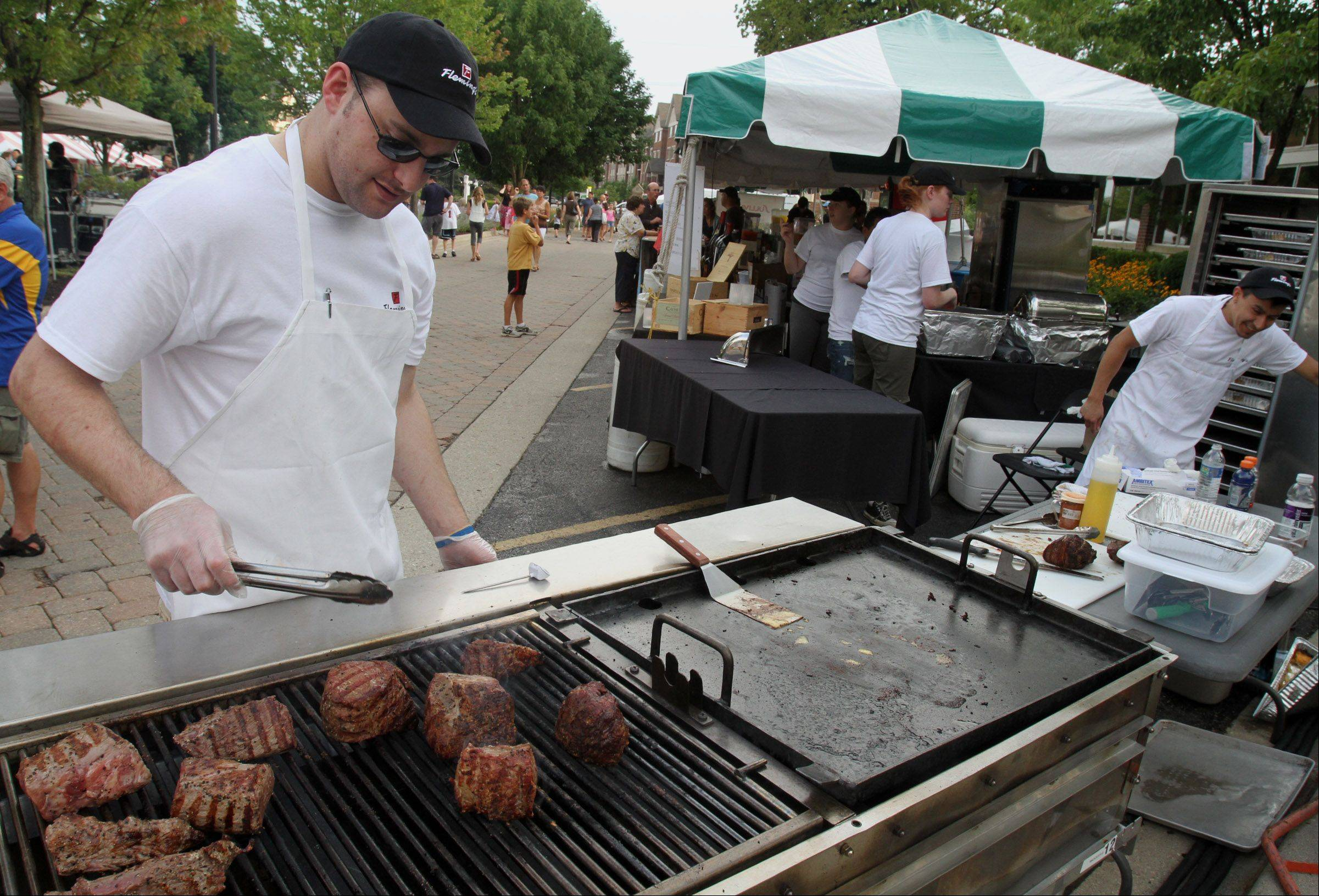 George LeClaire/gleclaire@dailyherald.coBen Knapp of Lake Barrington, a student chef for Fleming's Prime Steakhouse and Wine Bar, in Lincolnshire, mans the steakhouse's grill at the annual Taste of Lincolnshire at Village Green.