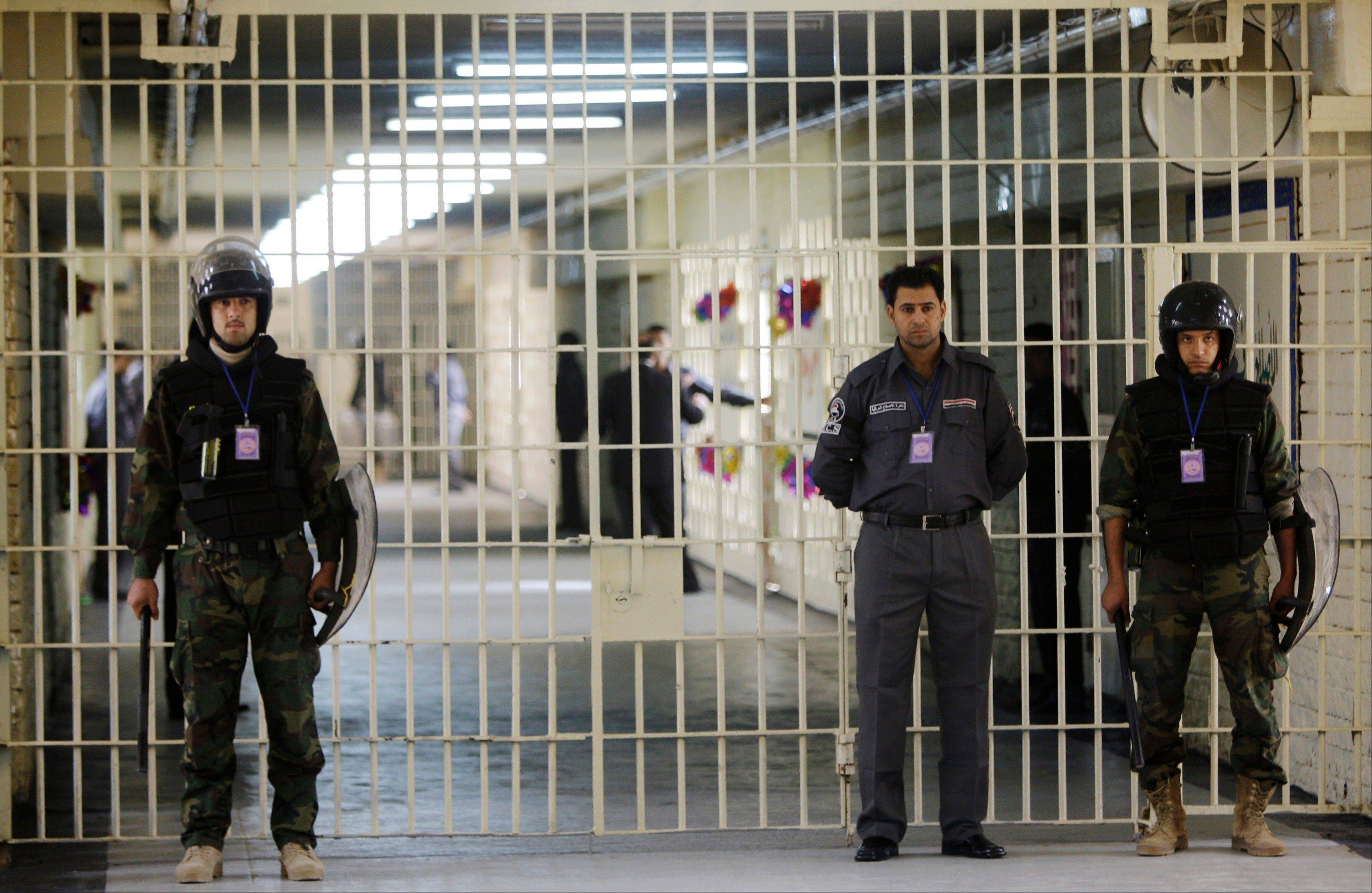In this Feb. 21, 2009 file photo, guards stand at a cell block at the renovated Abu Ghraib prison, now renamed Baghdad Central Prison and run by Iraqis in Baghdad. Late-night jailbreak attempts at two major prisons outside Baghdad have killed dozens, including at least 25 members of Iraq's security forces who battled militants armed with car bombs, mortars and machine guns, officials said Monday.