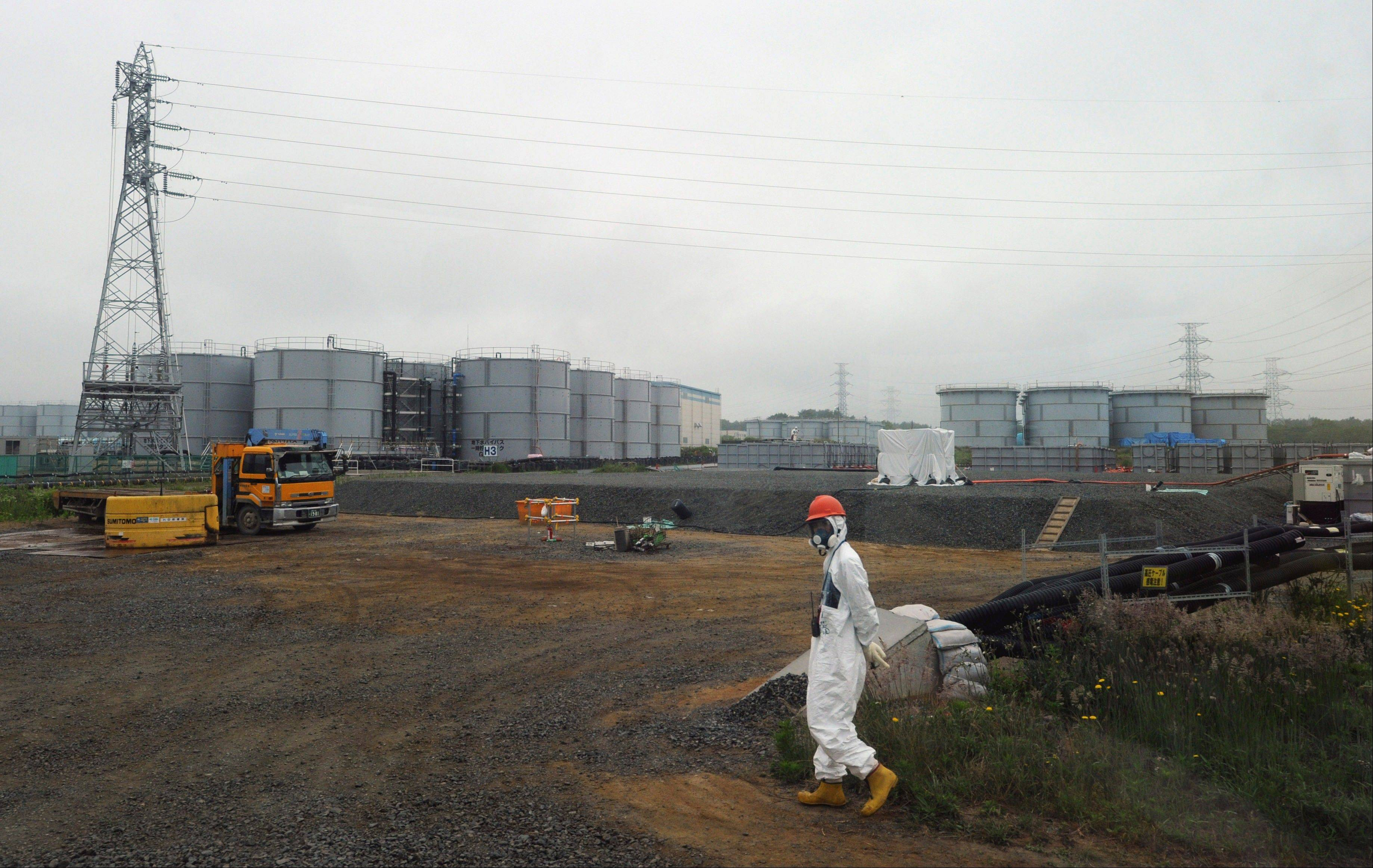 In this Wednesday, June 12, 2013 photo, a construction worker walks beside the underground water tank and water tanks at the Fukushima Dai-ichi nuclear plant at Okuma in Fukushima prefecture, Japan. A Japanese utility said its crippled Fukushima nuclear plant is likely to have leaked contaminated water into sea, acknowledging for the first time a problem long suspected by experts.