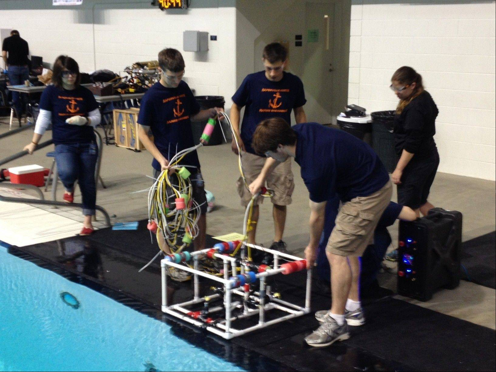 Carissa Cesarotti, Stuart Houston, Isaac Heine, Julie Ozols and Konrad Hausman, all members of Naperville North's marine engineering team, test their underwater remotely operated vehicle in a pool before competing in June in an international competition that mimics an underwater scientific lab. The team placed 19th out of 30 high schools from across the world.