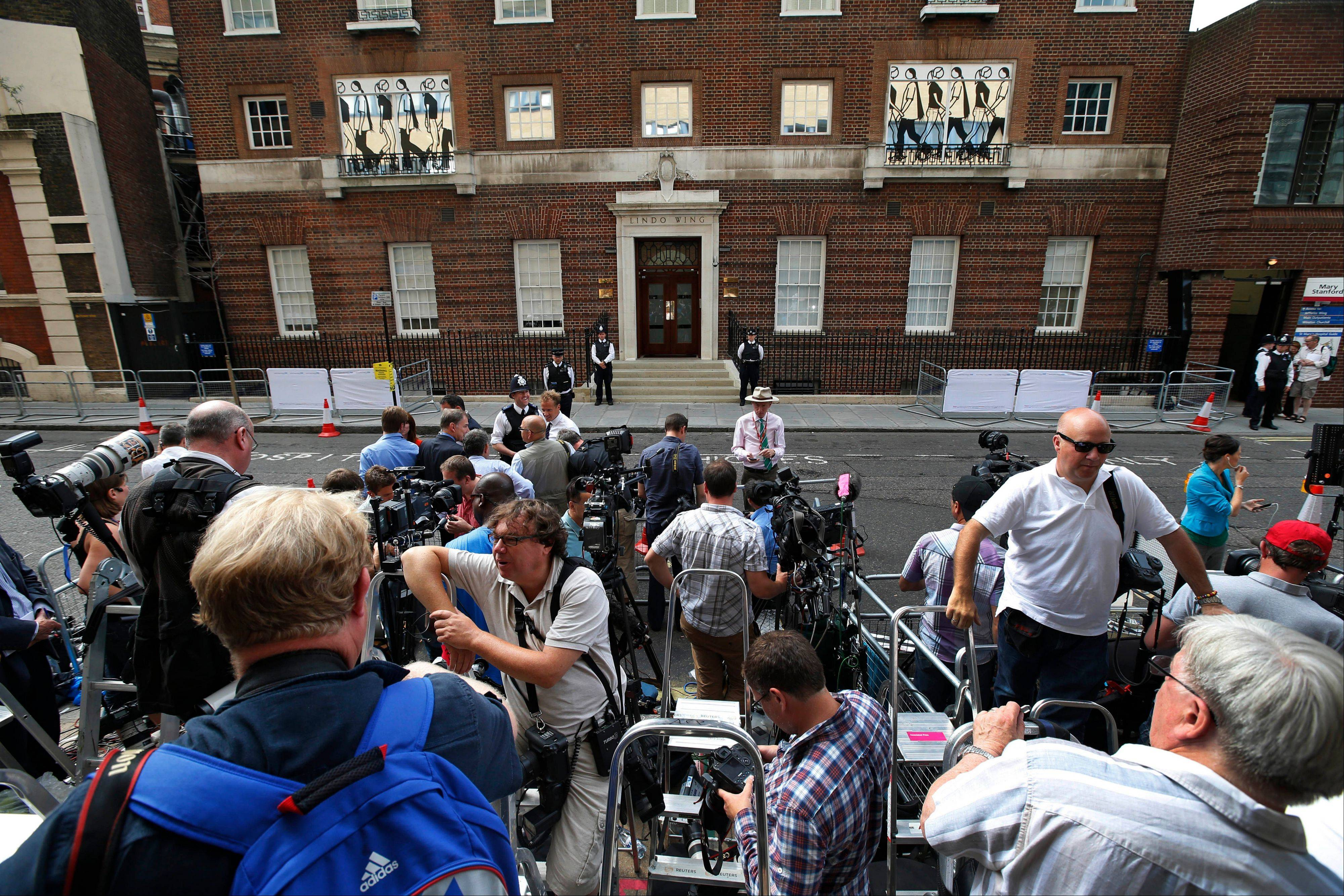 Members of the media wait across from St. Mary's Hospital exclusive Lindo Wing in London, Monday.