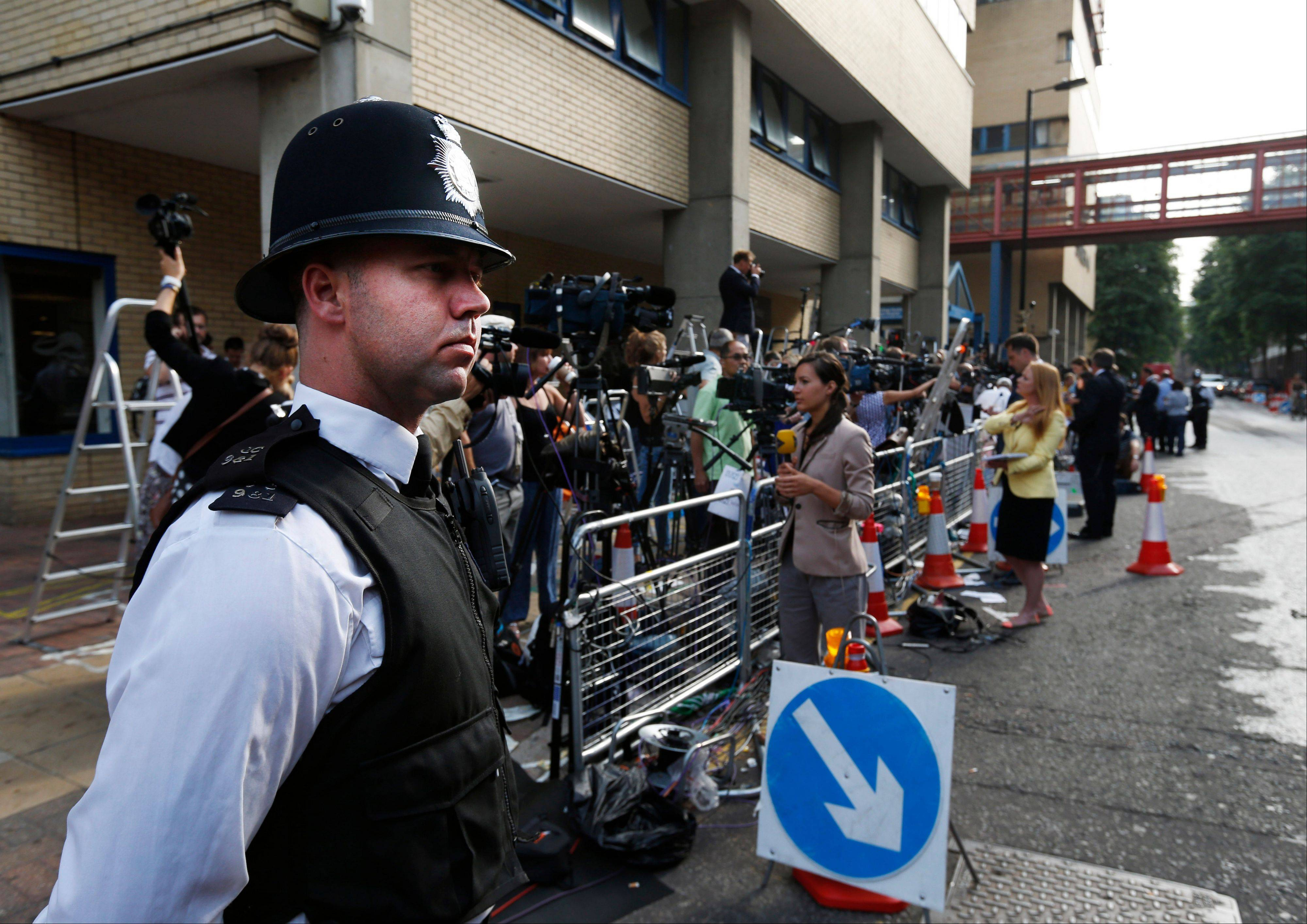 Backdropped by members of the media, a British police officer stands across the entrance of St. Mary's Hospital exclusive Lindo Wing in London, Monday.