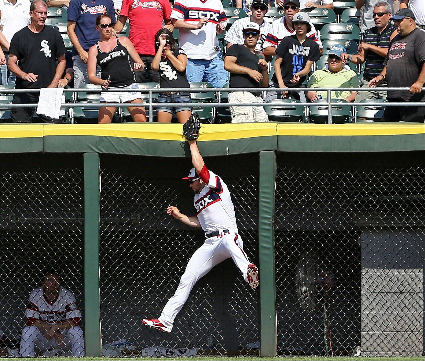 White Sox left fielder Casper Wells robs Atlanta Braves' Reed Johnson of a home run in the eighth inning as the White Sox defeated the Braves 3-1 in a baseball game in Chicago, Sunday, July 21, 2013.