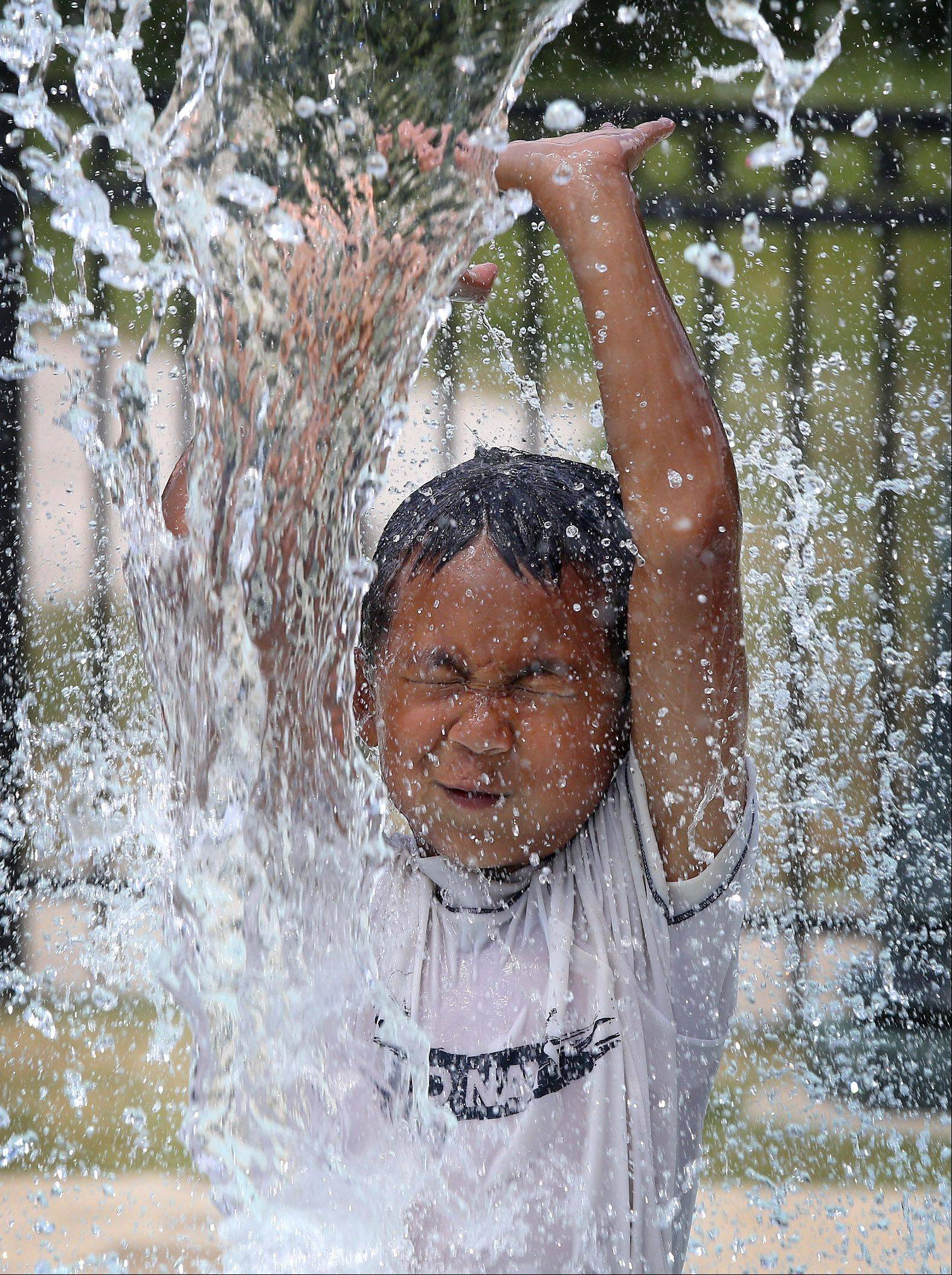 Jeremiah Hettich, 7, of Old School Montessori in Grayslake, plays at the Grayslake Park District Spray Park Tuesday. The hot, humid weather made it feel like it was over 100 degrees.