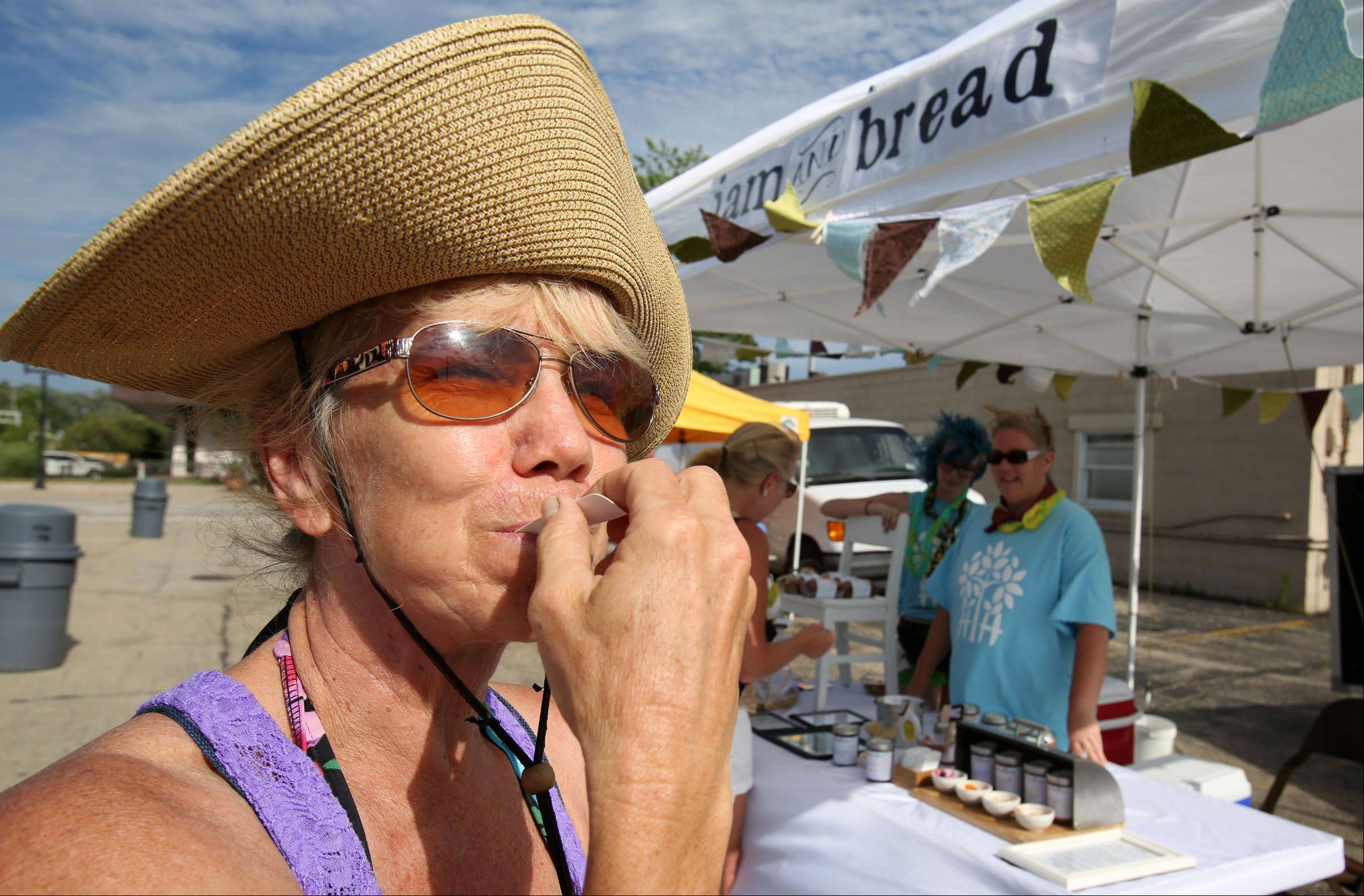 "Patti Heigert, of Mundelein, has her hat folded back from a strong gust as she tastes jam from Aolcomb Hollow Bread and Jam during ""Hawaiian Day"" at the Mundelein Farmers Market on Friday. The market is open Friday's from June 14 through October 11 from 3 to 7 p.m."