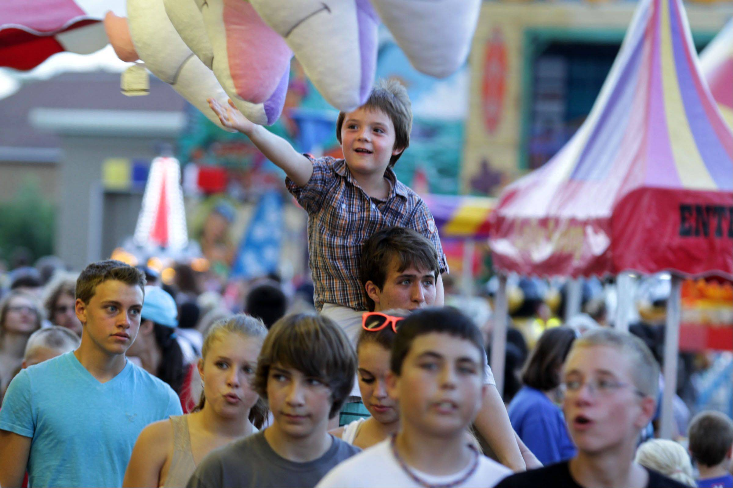 Parker Lambert reaches for a carnival prize while on the shoulders of his stepbrother, Grant Rodger, at the first day of Alpine Fest in Lake Zurich on Friday.