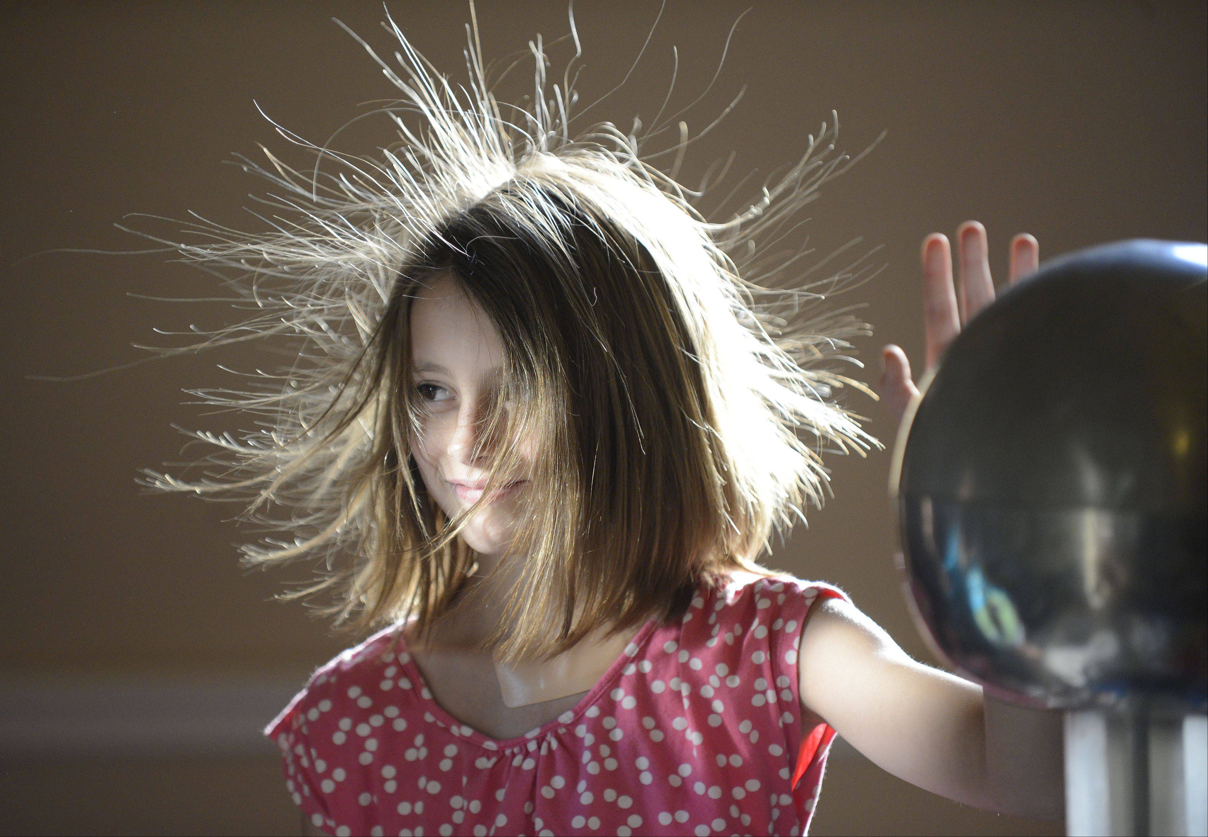 "Georgi Ann Kerwin, 8, of Hampshire, gets charged up during the ""Lights! Camera! Action!"" physics program presented by The Science Alliance for the Ella Johnson Memorial Public Library in Hampshire Tuesday. Children with all different hair lengths got to try it out and see how their hair was affected by the charging."