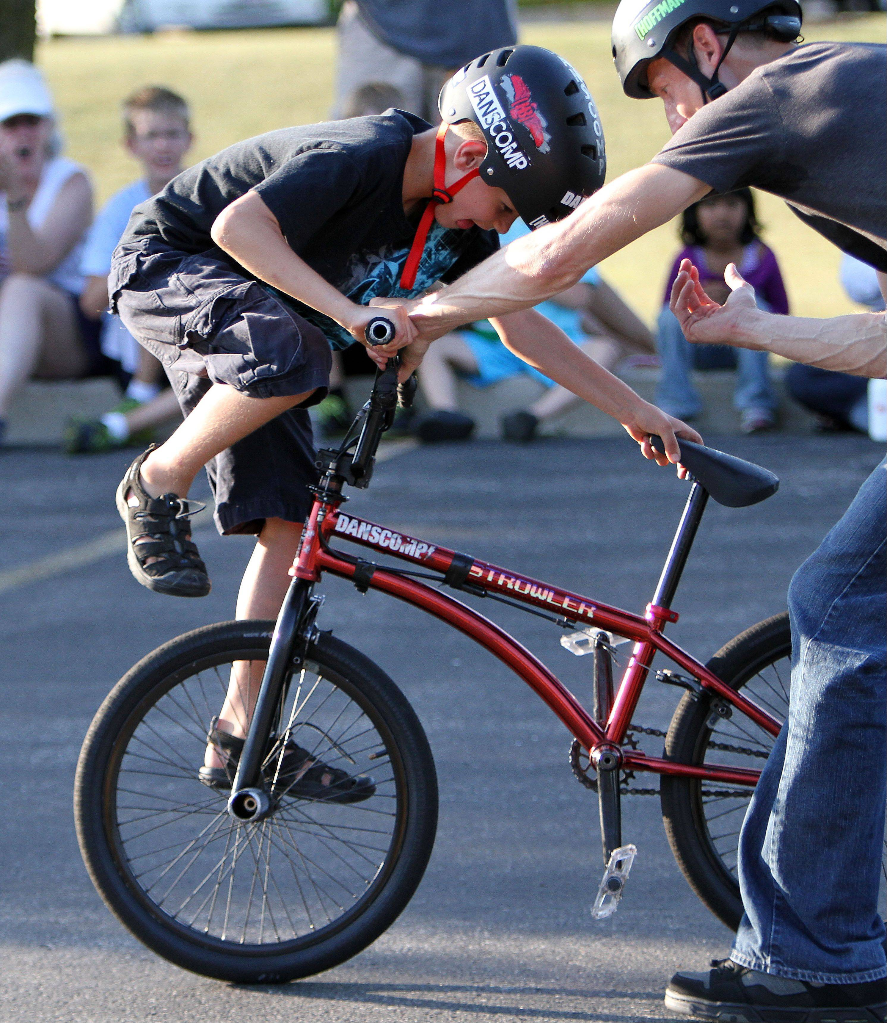 8-year-old Xander Jakubisin of Third Lake learns a trick from BMX expert Matt Wilhelm during a performance at Grayslake Public Library Wednesday. Wilhelm has won numerous contests including X-Games and national championships.