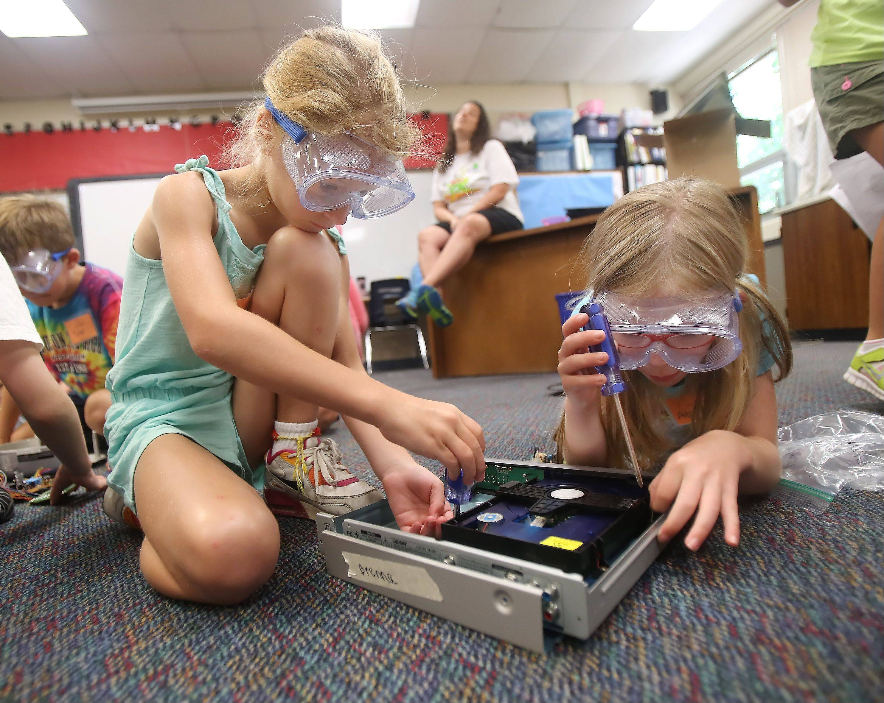 Seven-year-olds Brenna Hornsey, left, and Atalhea Herman, both of Libertyville, take a computer apart during Camp Invention Wednesday at Rockland School in Libertyville. The Libertyville School District 70 summer program featured creative activities for elementary school age students.