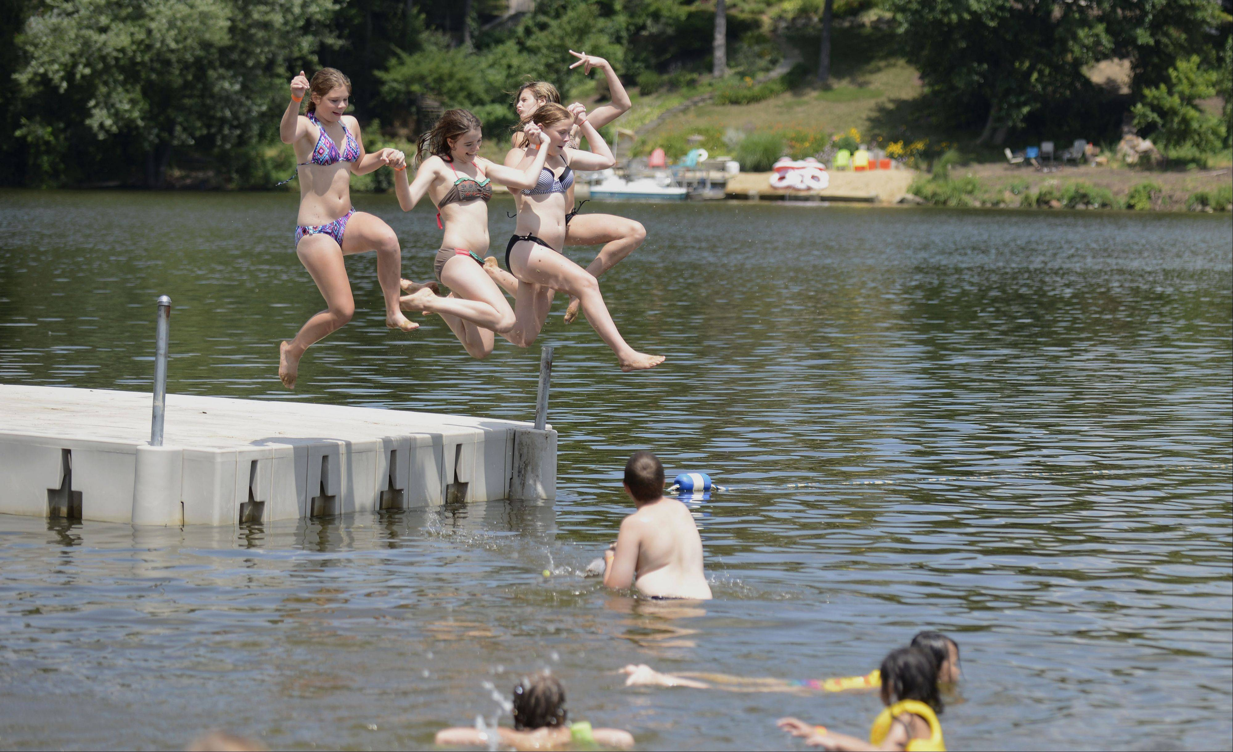 "Olivia Warchol, Tessa Morse, McKenna Warchol, and Niki DeVita, all 14 and from Algonquin, take a plunge hand-in-hand off the dock at Woods Creek Lake in Lake in the Hills Thursday. DeVita says of the temperature, ""I like it�it's warm but refreshing."" Morse says, ""It's not too hot and not too cold,"" and Emily Warchol chimed in, ""It's just right."""