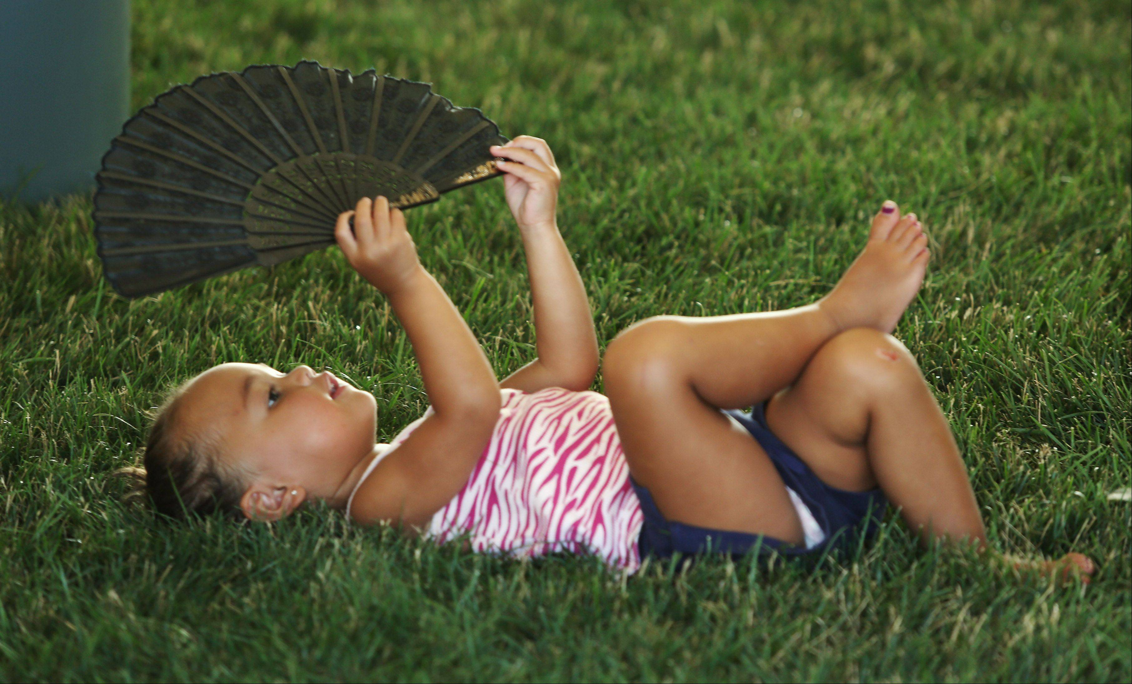 Abbie Glover, 2, of Round Lake Heights, keeps cool in the food tent with a fan during the Vernon Hills Summer Celebration at Century Park Thursday. The event included music, entertainment, food and amusement rides.