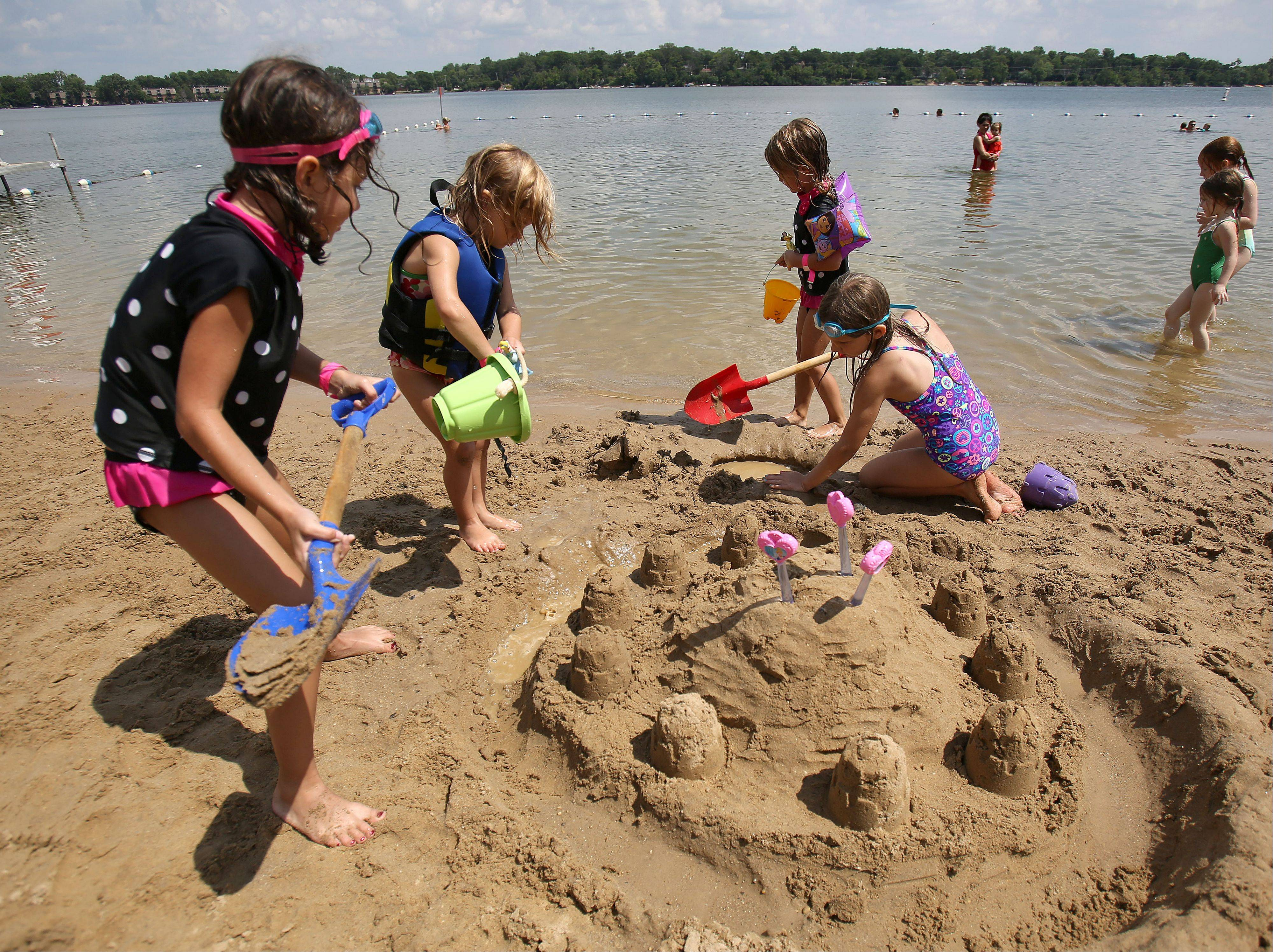 From left, Ellie Santuchi, 6, Kylie Carroll, 4, Ava Santucci, 4, and Kendra Carroll, 6, all of Cary, build a sandcastle at Paulus Park Beach in Lake Zurich Thursday.