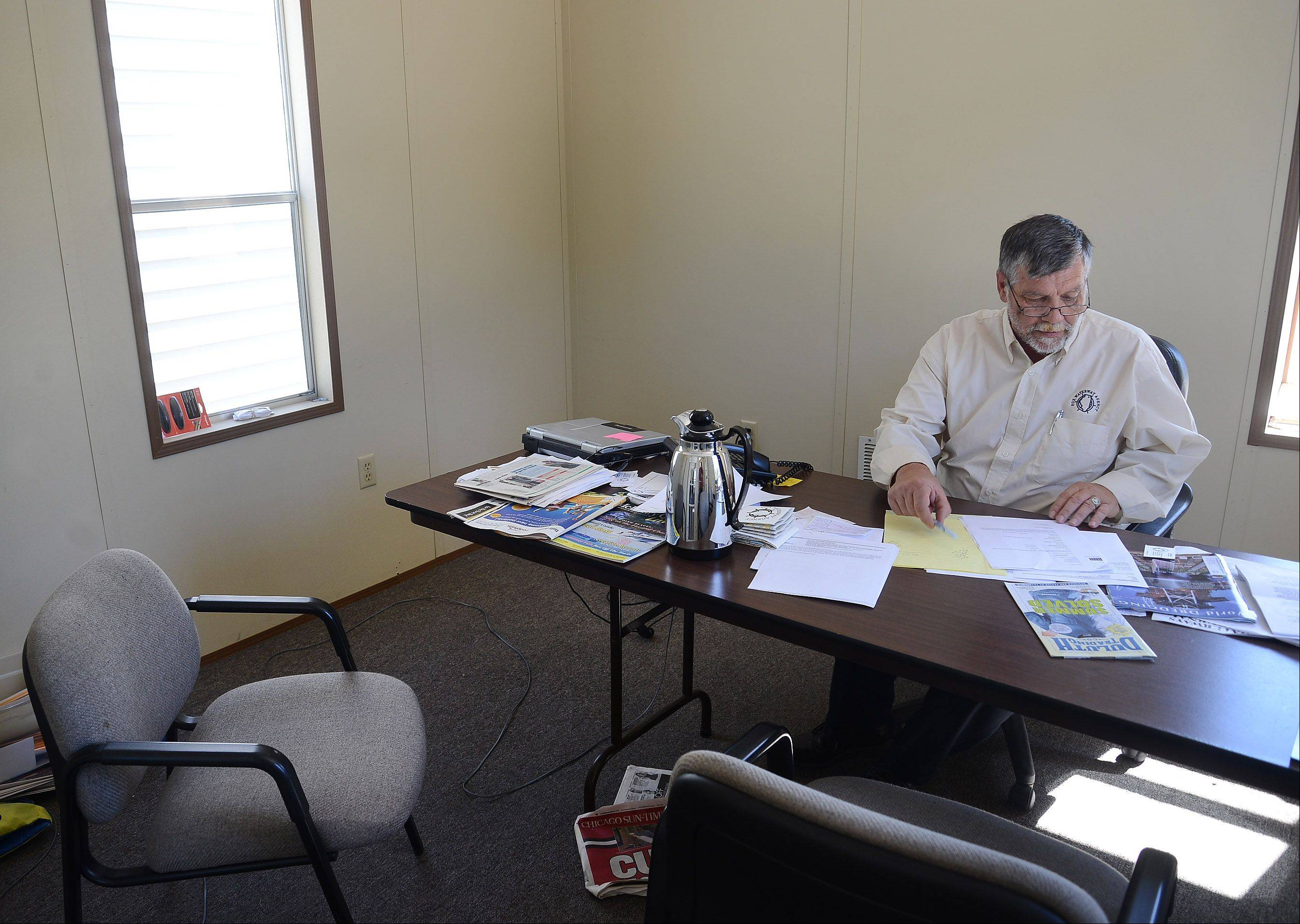 Fox Waterway Agency Executive Director Ron Barker inside his cramped office in the trailer where employees now work while waiting for flood repairs to be made to their office building in Fox Lake.