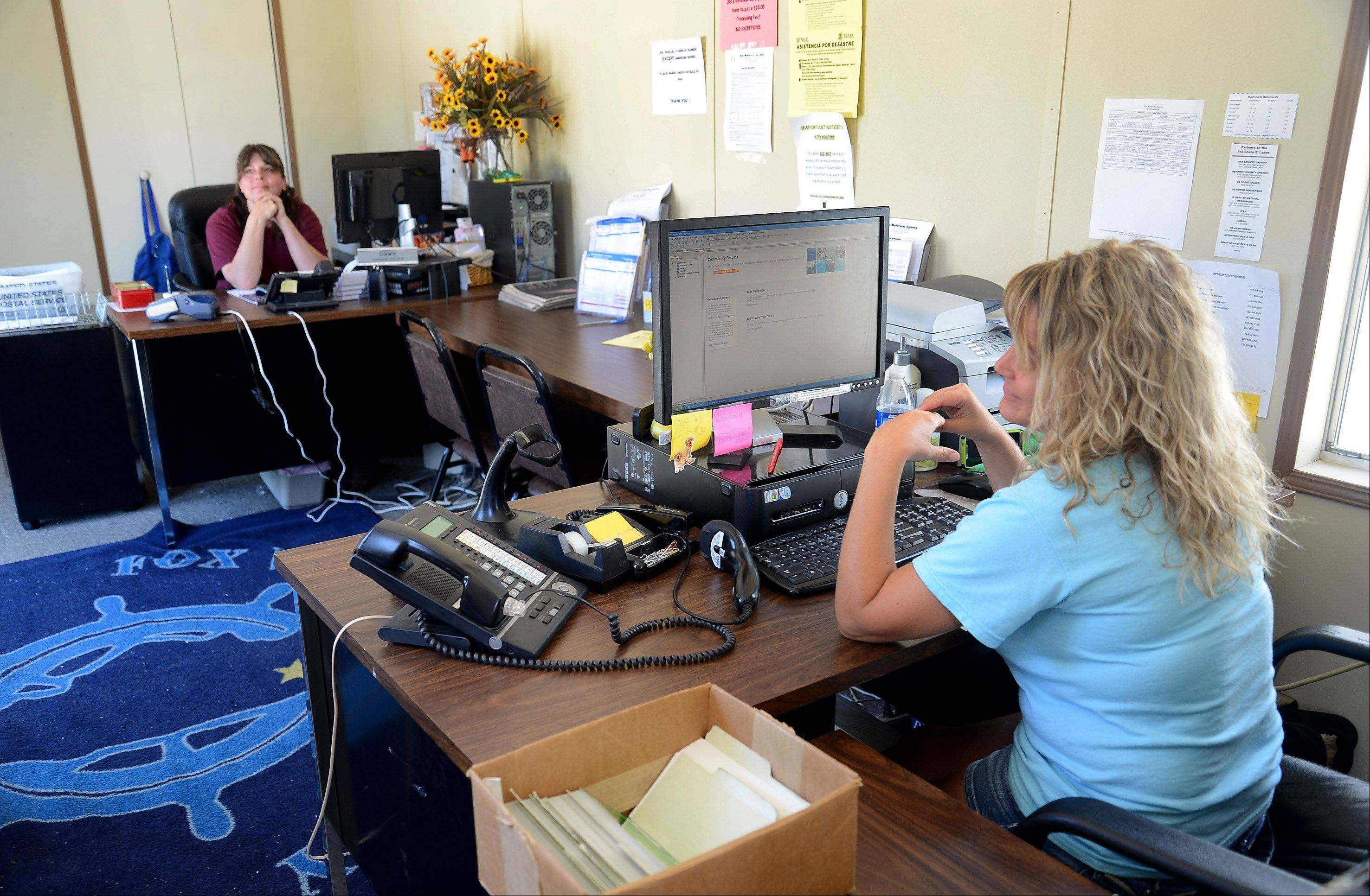 Fox Waterway Agency employees Dawn Miklitsch and Kristine Pearson working in the cramped trailer that is the agency's temporary home in Fox Lake.
