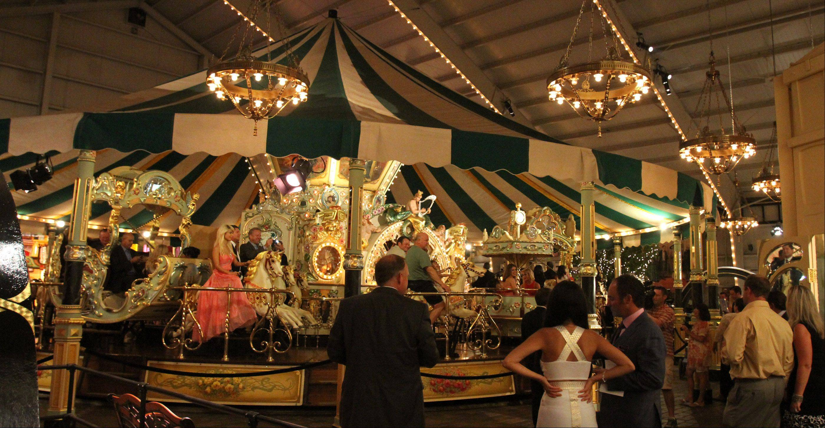 Guests watch as the elaborate Eden Palais Carousel twirls its occupants.