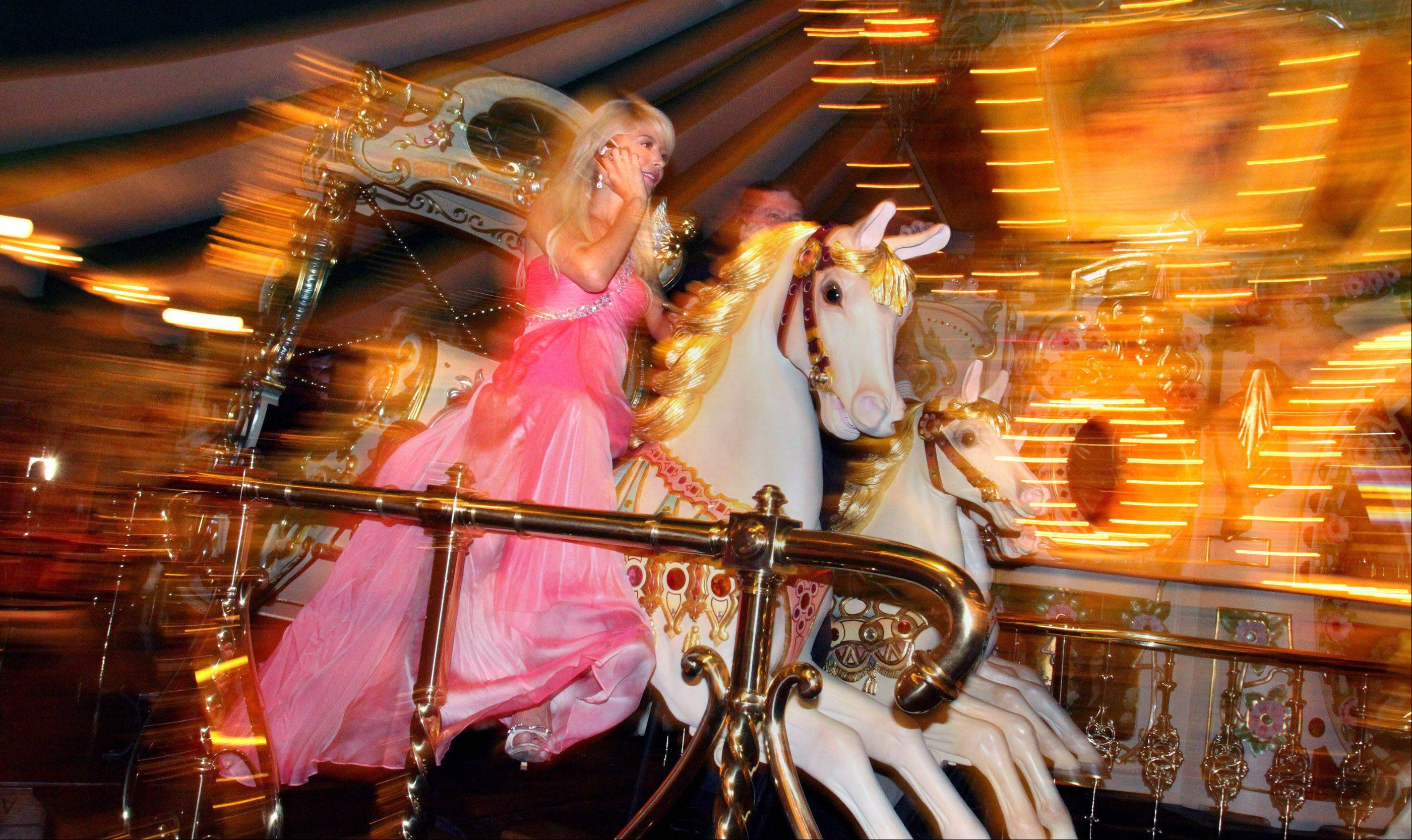Renata Costa raises funds using her cellphone while riding the Eden Palais Carousel.