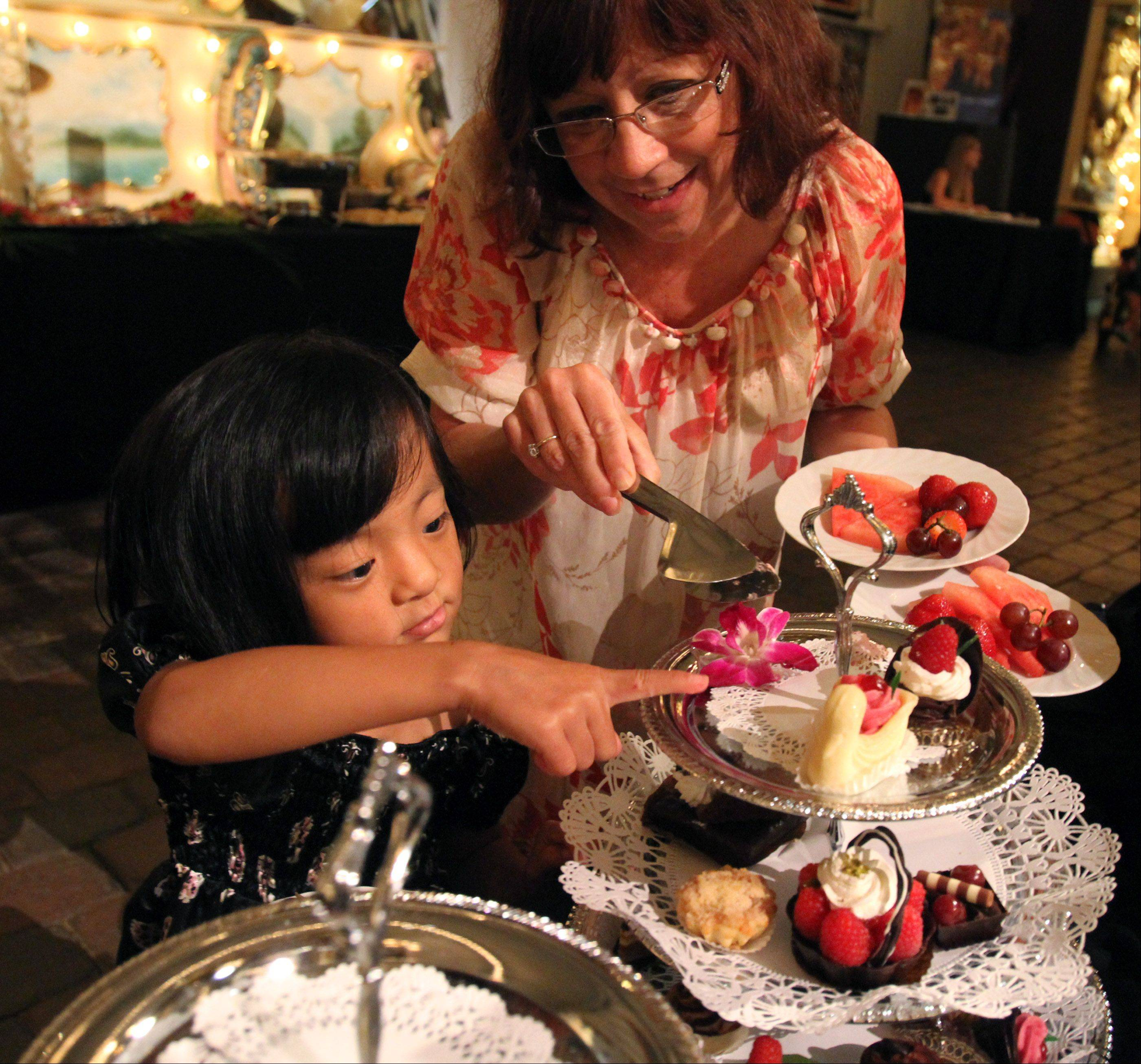 Lydia Wyse points out a dessert she'd like to try to her mother, Cheryl Wyse, at last year's fundraiser.