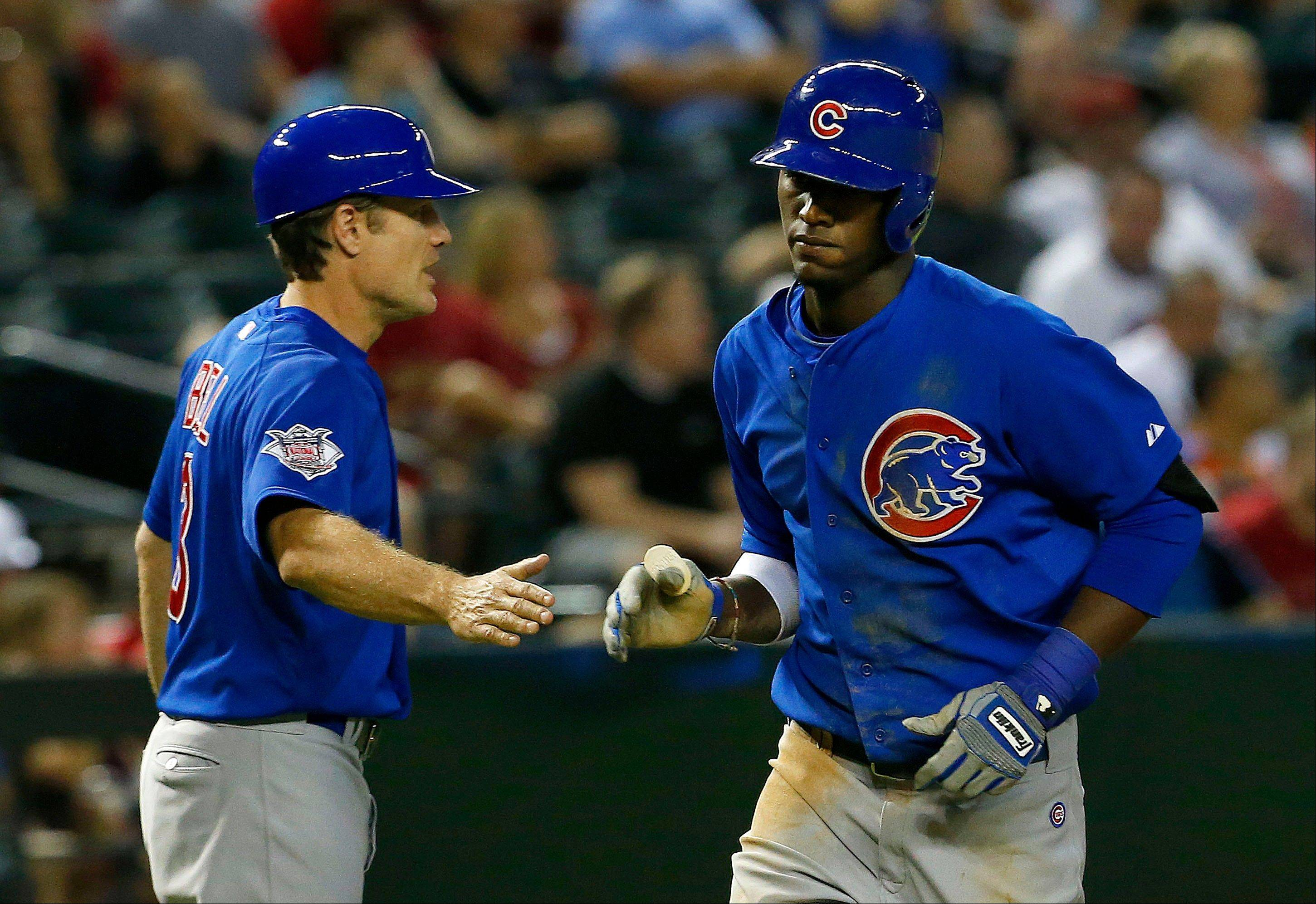 The Cubs' Junior Lake, right, shakes hands with third base coach David Bell after Lake's 2-run home run against the Arizona Diamondbacks in the fifth inning Monday in Phoenix.