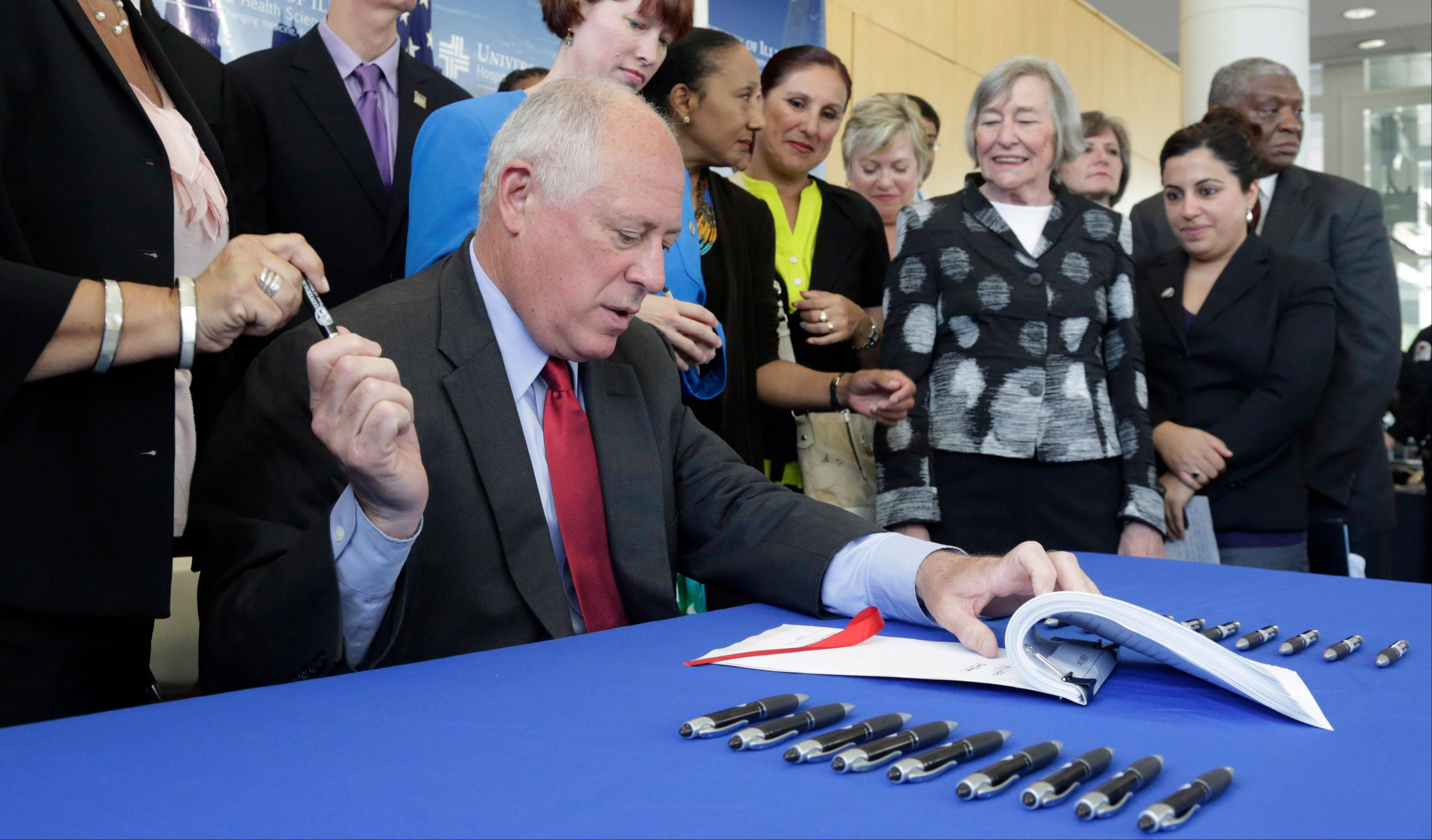 Gov. Pat Quinn signs a bill expanding Medicaid to cover low-income Illinois adults who don't have children at home, a big part of President Barack Obama�s health care law, Monday, July 22, 2013, at the University of Illinois at Chicago Outpatient Care Center in Chicago.