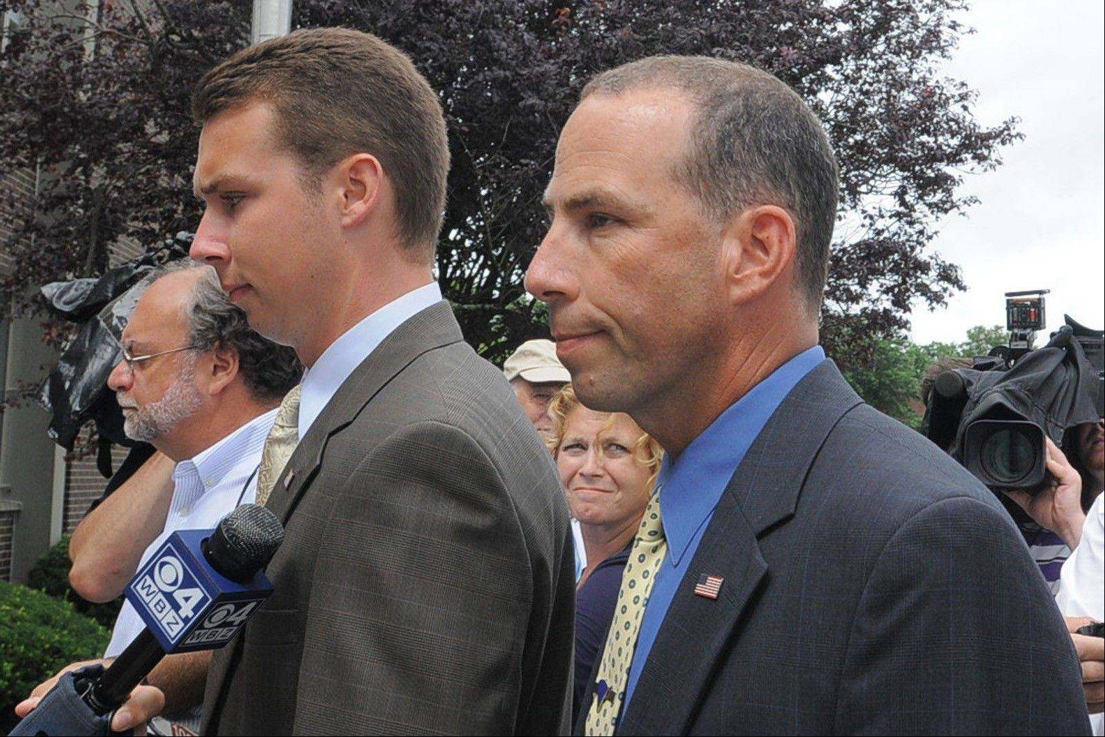 Massachusetts State Police Sgt. Sean Murphy, right, a tactical photographer, and his son Connor Patrick Murphy, arrive at State Police Headquarters for his hearing Tuesday to determine his duty status after he released images of the arrest of the Boston Marathon bombing suspect, in Framingham, Mass.