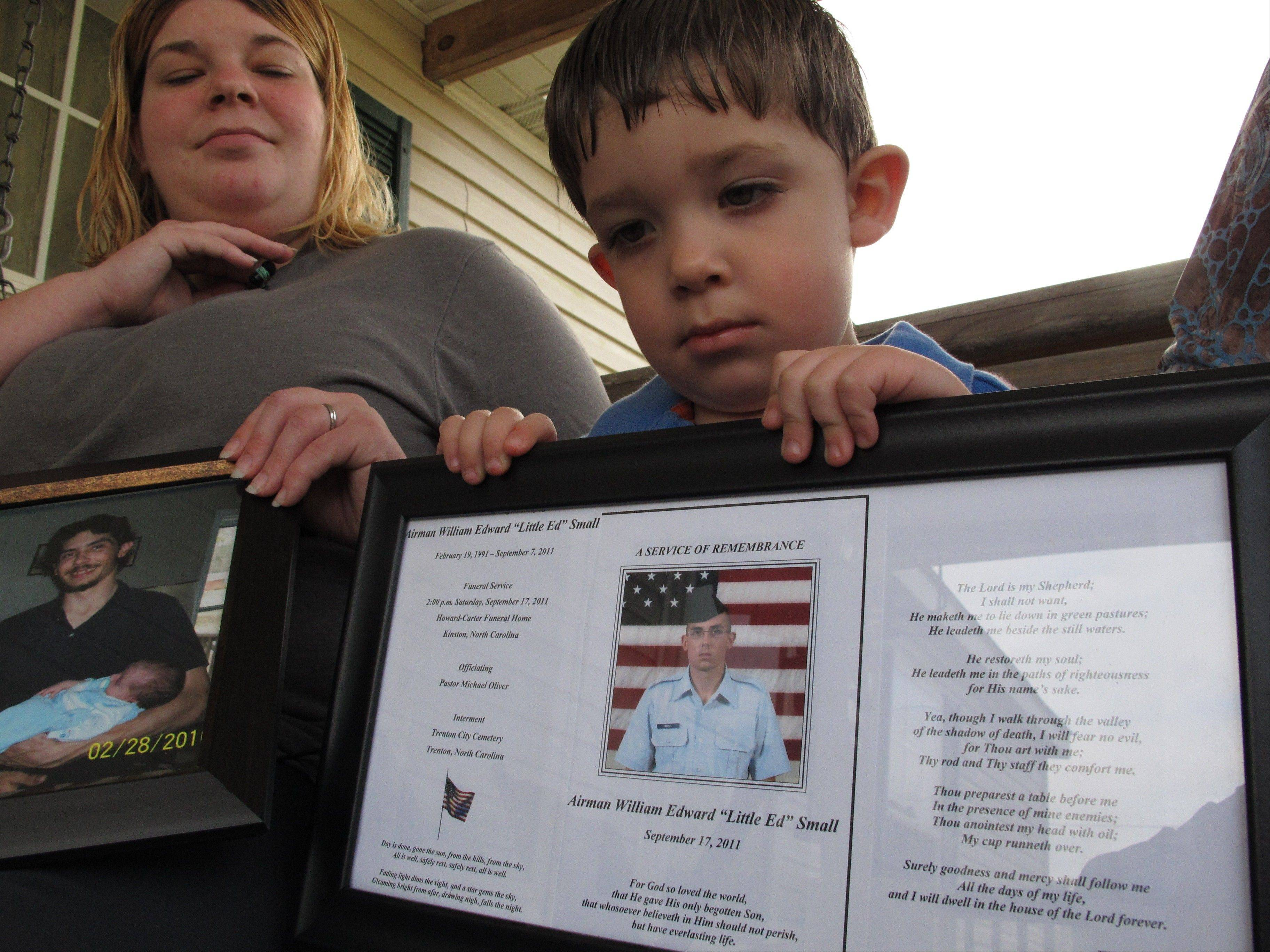 Shane Mercer points to a photo of his father, Airman Will Small, as his mother Alecia Mercer looks on at their home in Kinston, N.C. Small, whose organs were donated to four patients after he died, had at least two untreated raccoon bites several months before he became sick, and tests confirm his rabies-infected kidney led to a recipient's death.