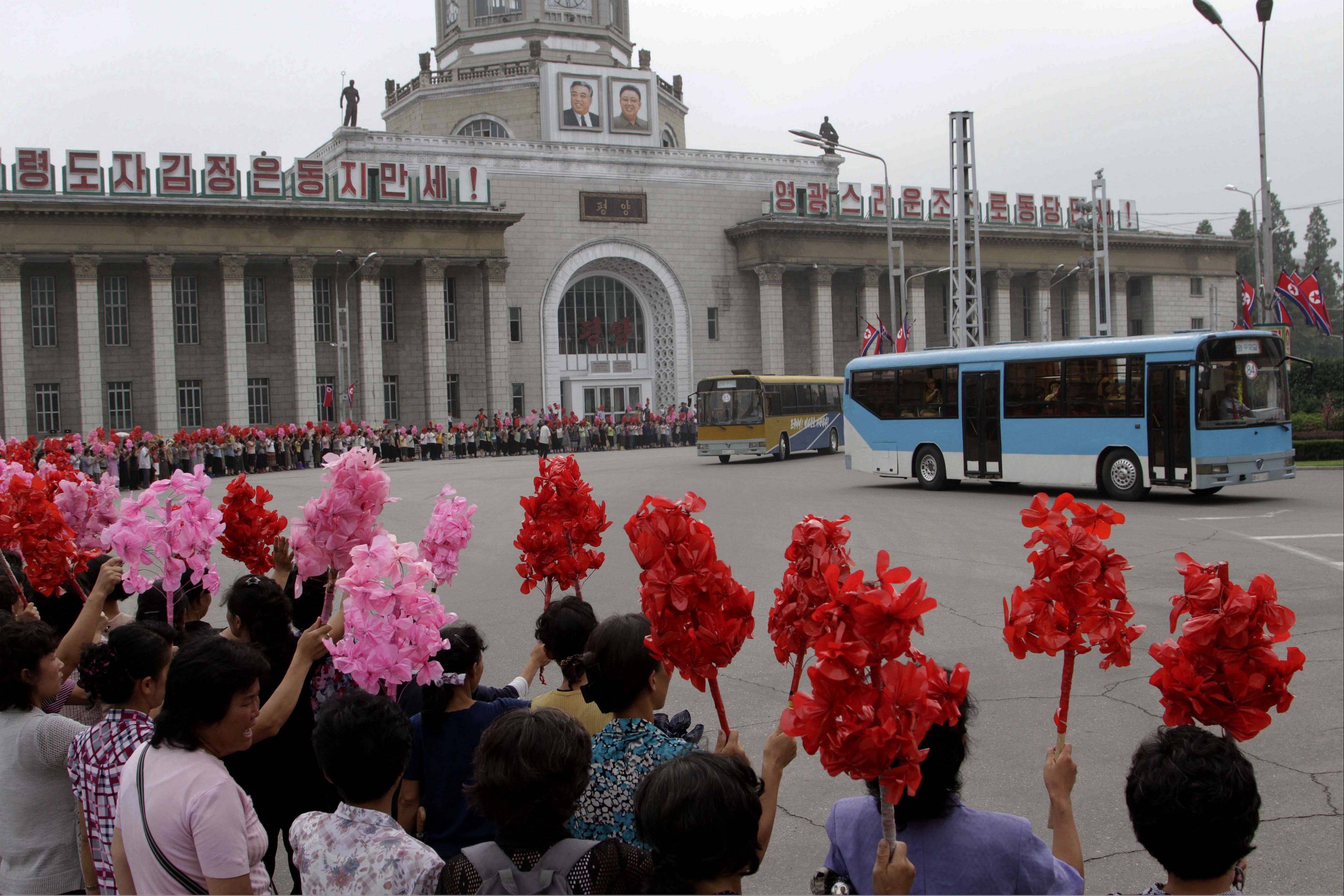 North Koreans welcome veterans of the Korean War as they pass by inside buses after arriving at the Pyongyang railway station Tuesday. Veterans arrived in Pyongyang as the country prepares to mark the 60th anniversary of the end of the Korean War on July 27.