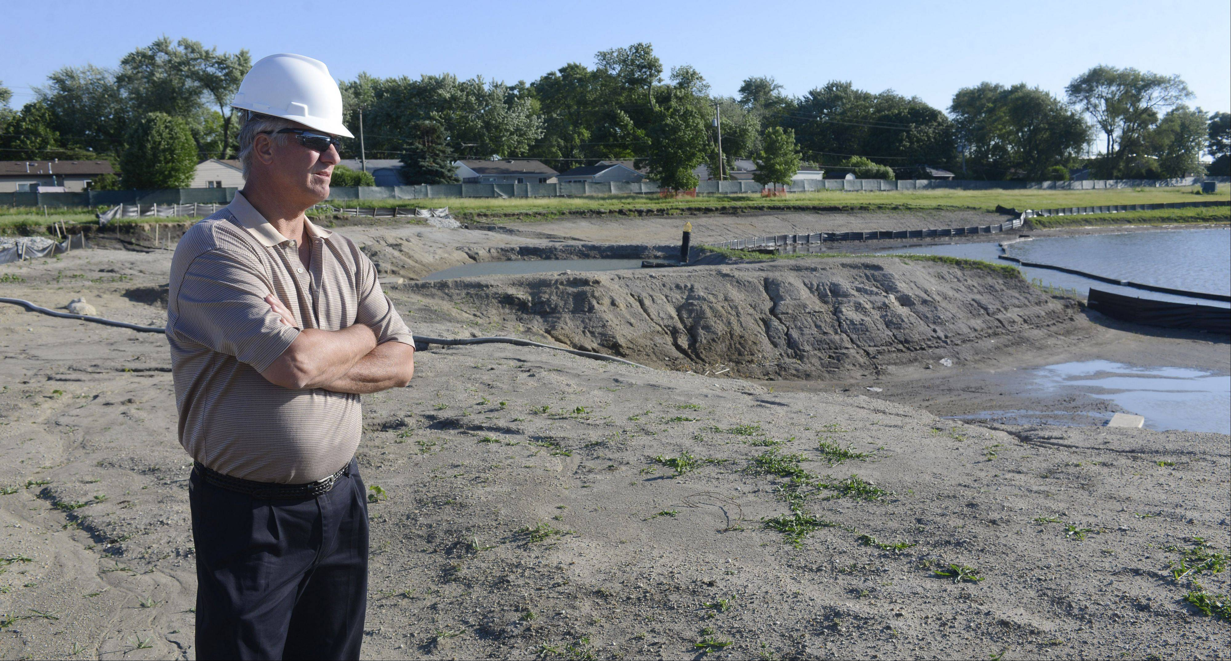 Keith Pecka, president of the Wheeling Park District board of commissioners, views progress made during the past year at Heritage Park. Heritage Lake is at the right.