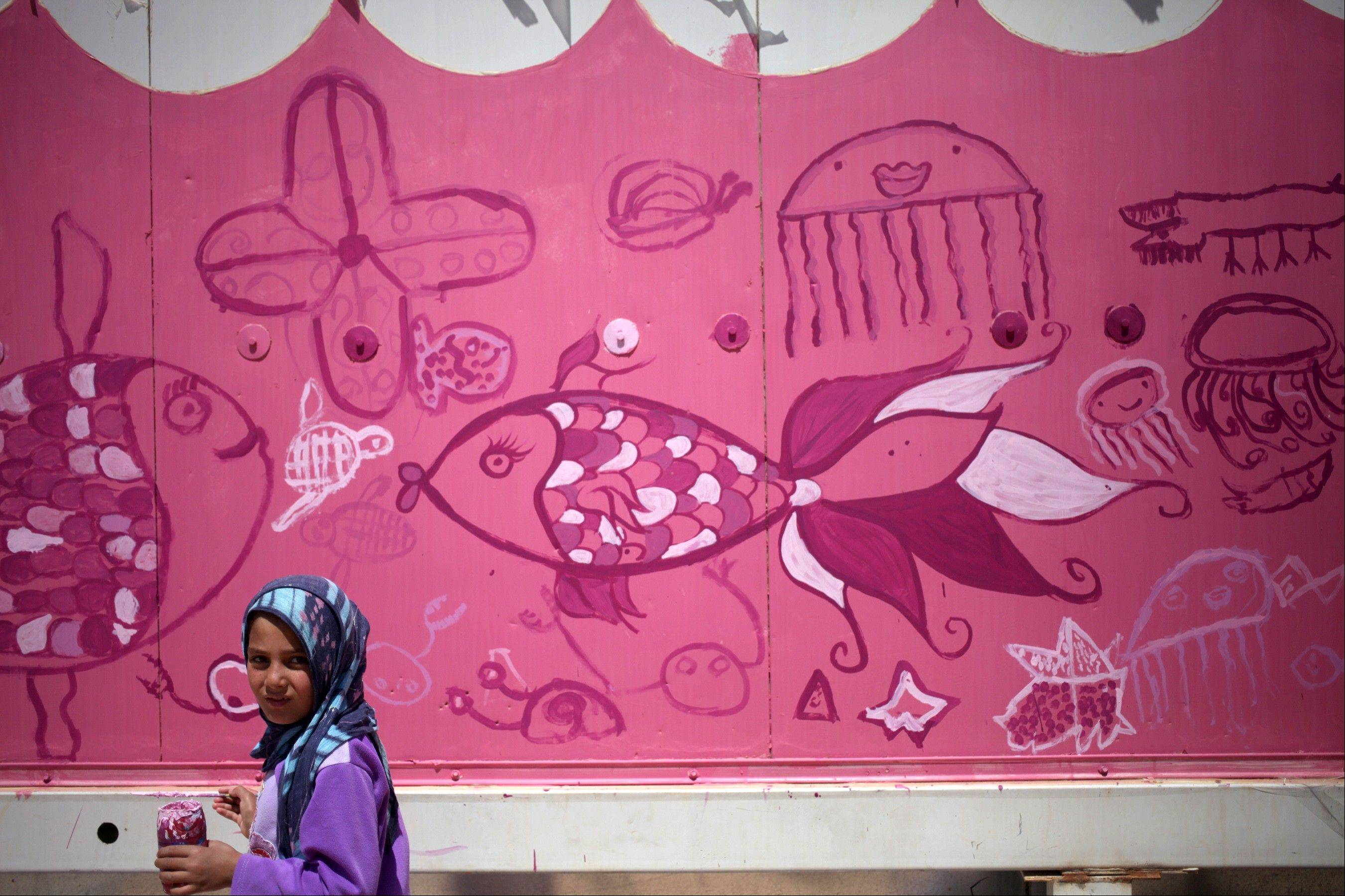 A Syrian refugee girl pauses while painting a mural on the wall of one of the public bathrooms to make it look like an aquarium, at Zaatari refugee camp, near the Syrian border, in Mafraq, Jordan, Tuesday, July 23, 2013. A U.S.-based artist is leading children haunted by the conflict to paint buildings and walls at the crowded camp with murals expressing their lives and hopes.