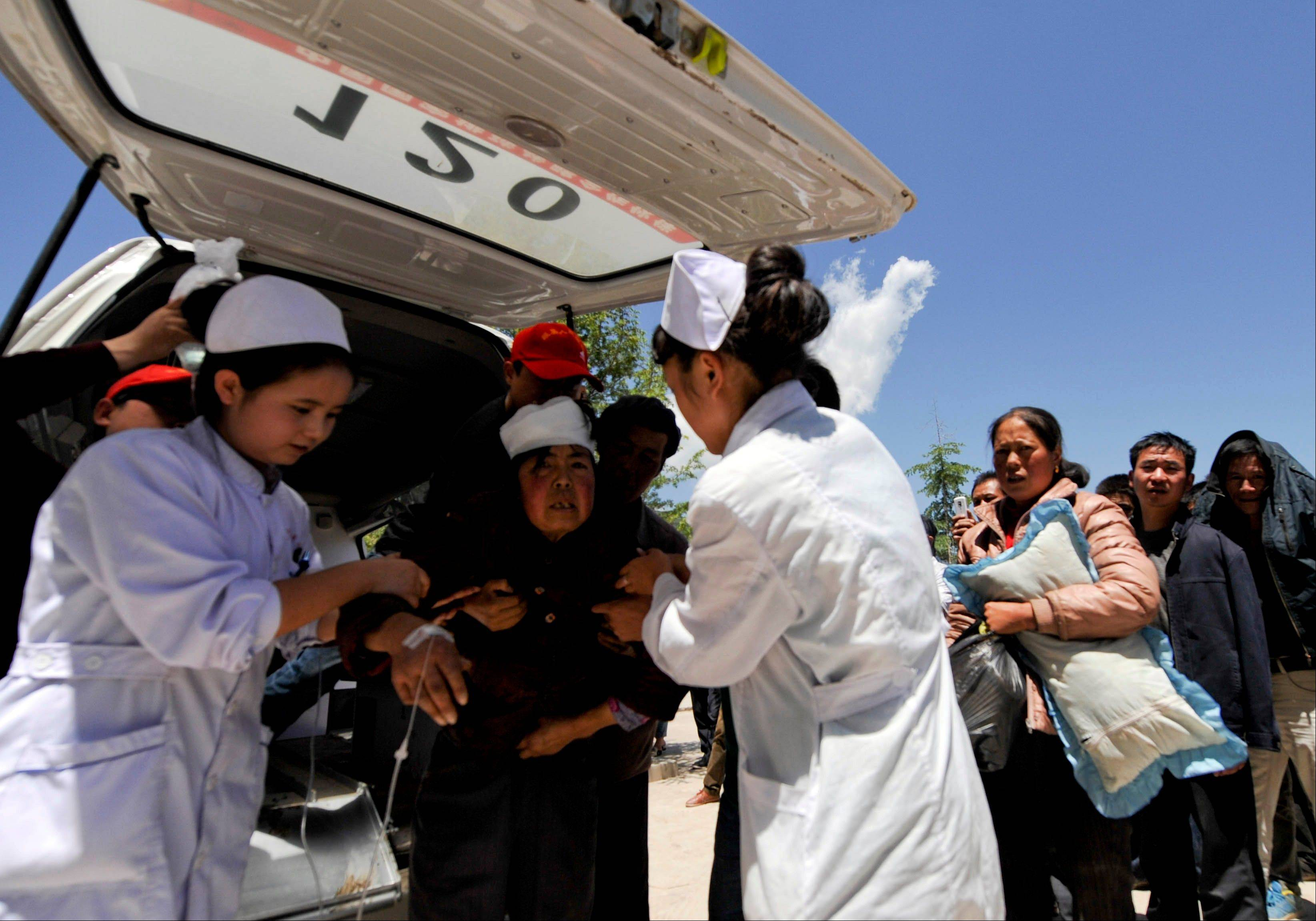 A woman injured in an earthquake is helped by medical workers in Minxian county in Dingxi city in northwest China's Gansu province on Monday, July 22, 2013. A strong earthquake that shook an arid, hilly farming area in northwest China sparked landslides and destroyed or damaged thousands of brick-and-mud homes Monday, killing at least 94 people and injuring more than 1,000, the government said.