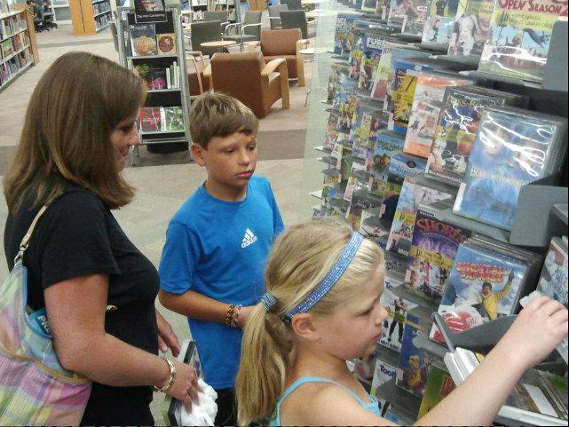 Janet Adkisson and her children, Payton and Ashley, search for DVDs at the Vernon Area Public Library in Lincolnshire. Audiovisual circulation has increased since the library reopened in late May, officials say.