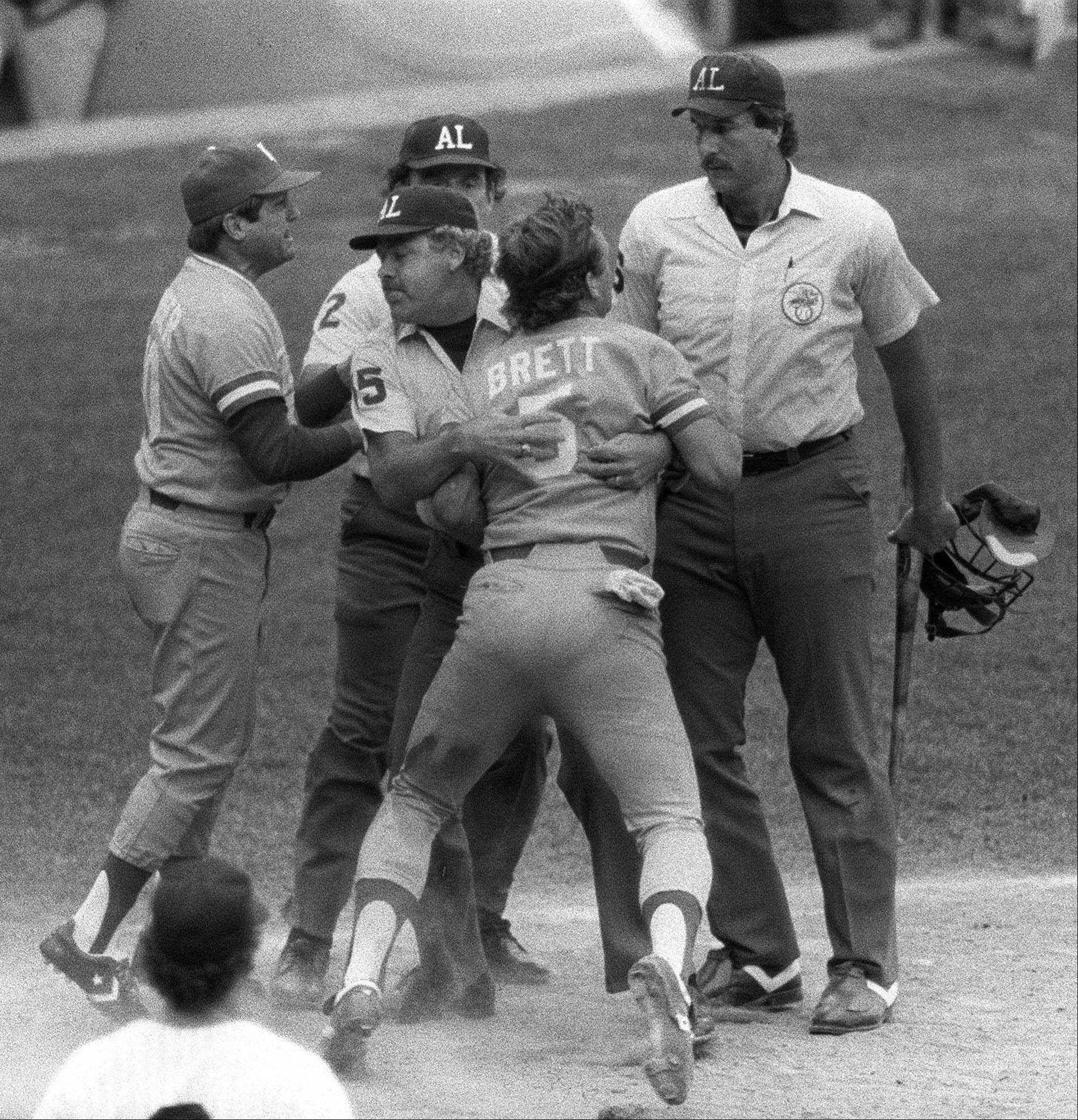 The Royals' George Brett, center, is restrained by umpire Joe Brinkman after his bat, held by umpire Tim McClelland, right, was ruled illegal because of the amount of pine tar on the handle. Brett had hit a home run that would have won the game against the Yankees but was instead called out.