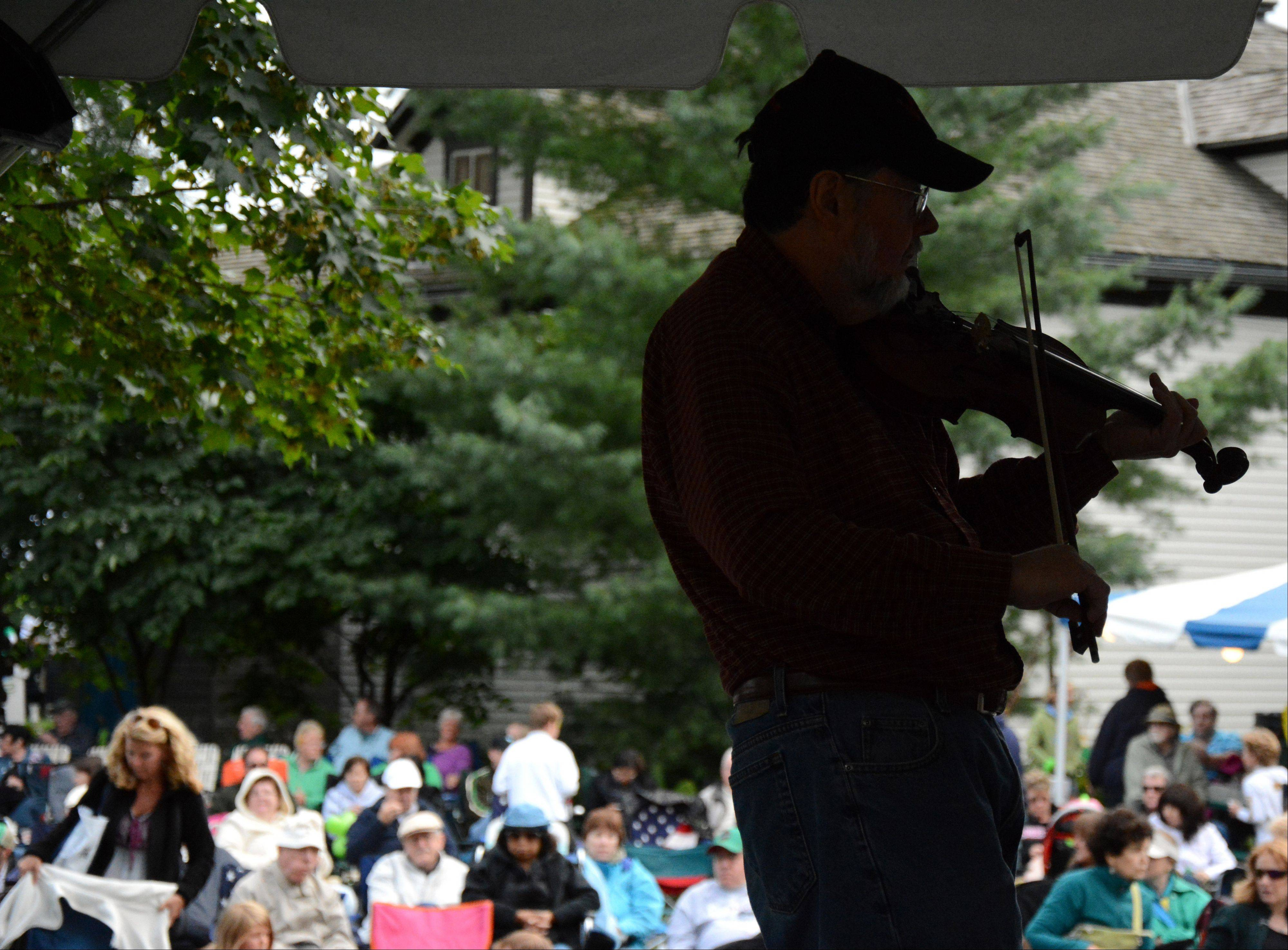 Dave Dvorak/ddvorak@dailyherald.comRick Versas, of Chicago, plays fiddle with band Mulligan Stew as a large crowd looks on at the Arlington Heights Irish Fest Saturday, July 27.