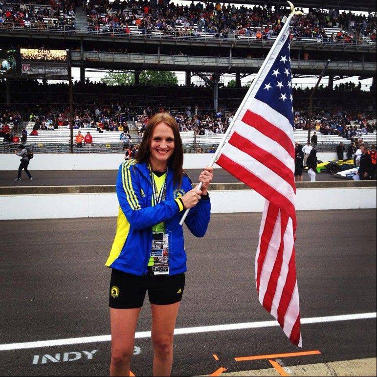 Kimberly Grauer waves the flag she carried while leading a group of runners at the Indianapolis 500 in memory of the Boston Marathon attack.
