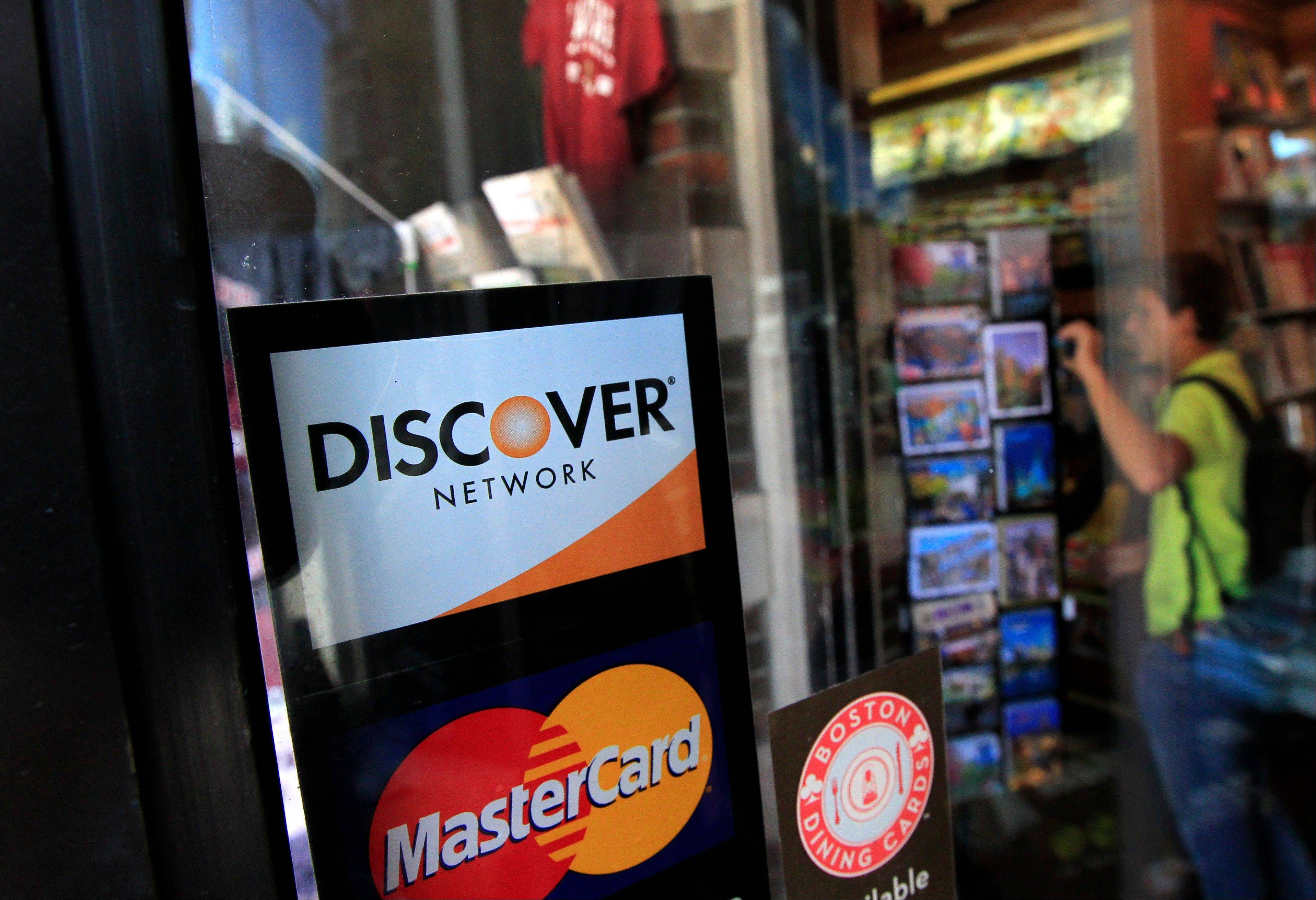 A Discover logo in the window at the entrance of a shop in Cambridge, Mass.