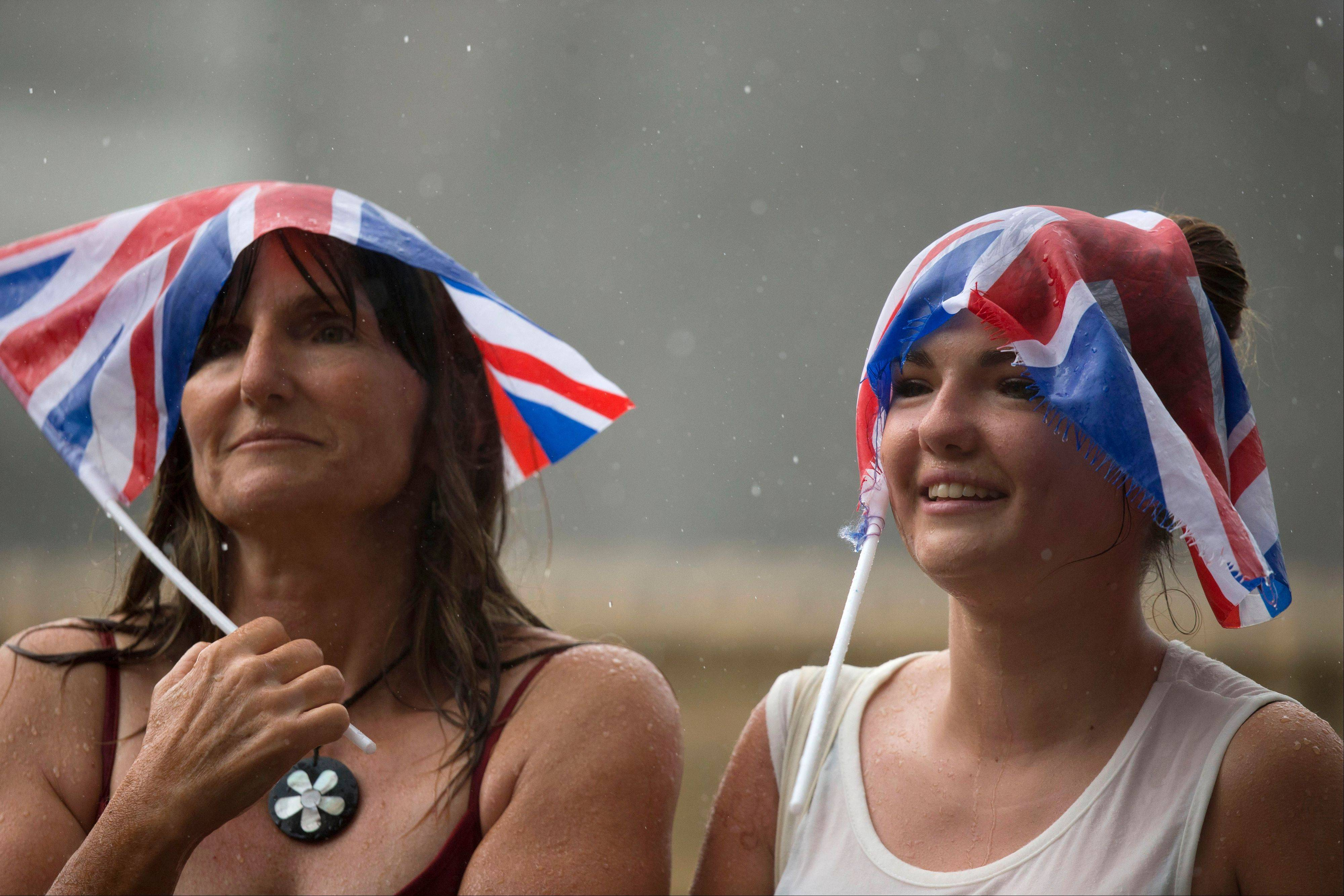 Royal supporters use Union flags to shelter from the rain as they await the departure of Britain's Prince William, Kate, Duchess of Cambridge and the Prince of Cambridge, outside the entrance of the private Lindo Wing at St. Mary's Hospital in London.