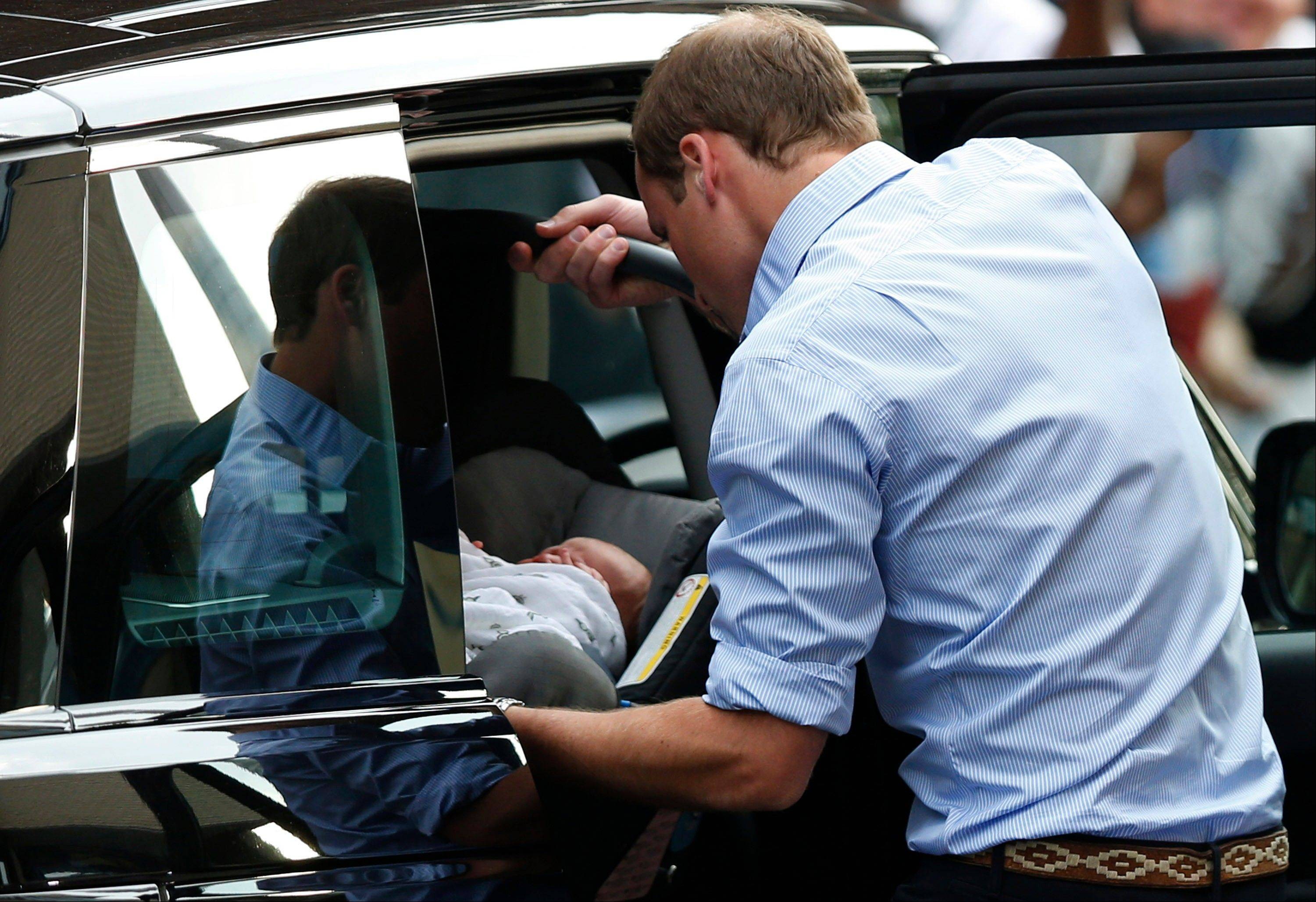 Britain's Prince William places carefully the Prince of Cambridge into a car, Tuesday July 23, 2013, as they leave St. Mary's Hospital exclusive Lindo Wing in London.