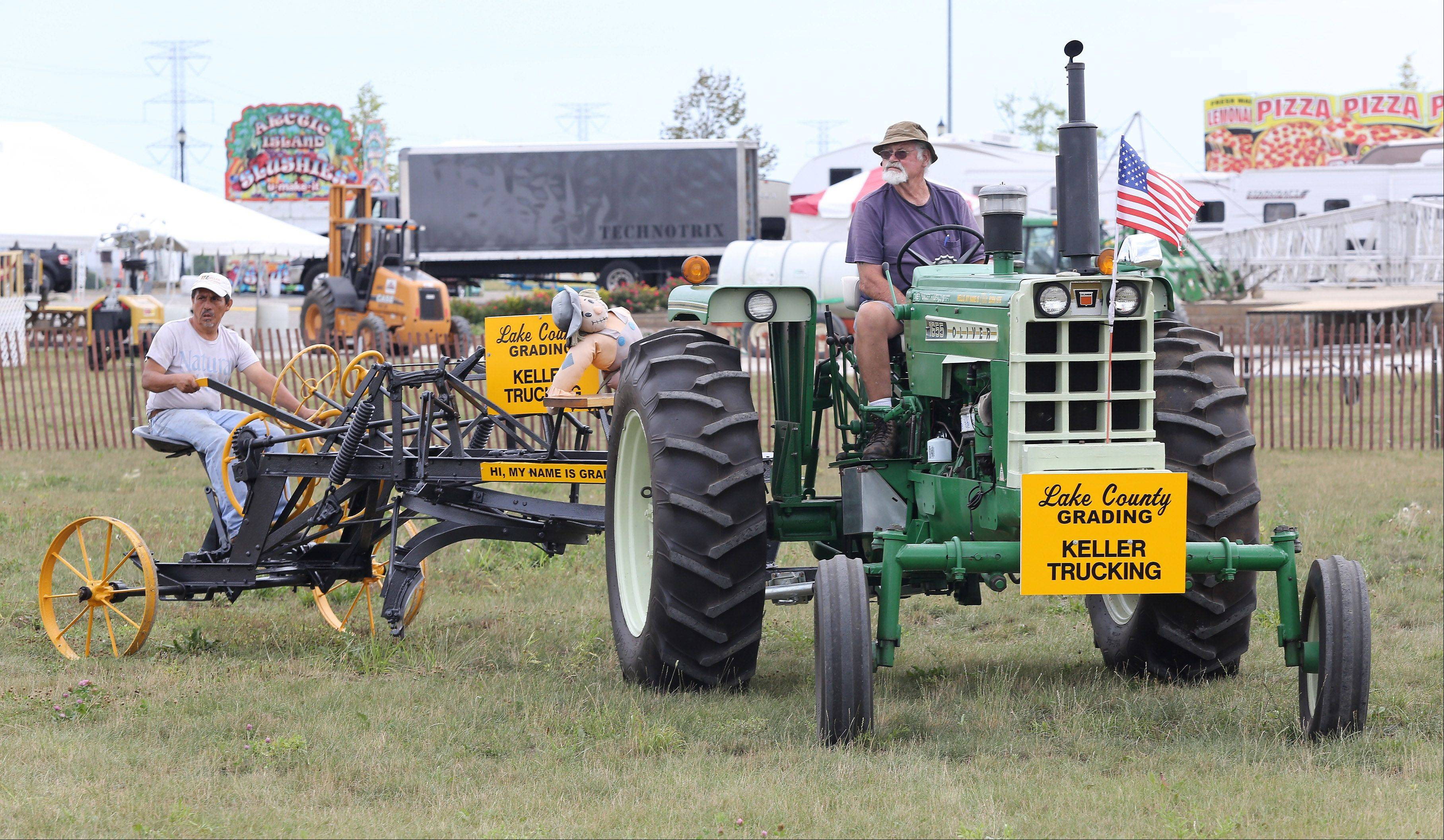 John Paulson of Keller Trucking, right, and Luis Diaz drive a 1976 Oliver tractor with a 1918 grader into the Lake County Farm Heritage Association, Inc. exhibit Tuesday at the Lake County Fair in Grayslake.