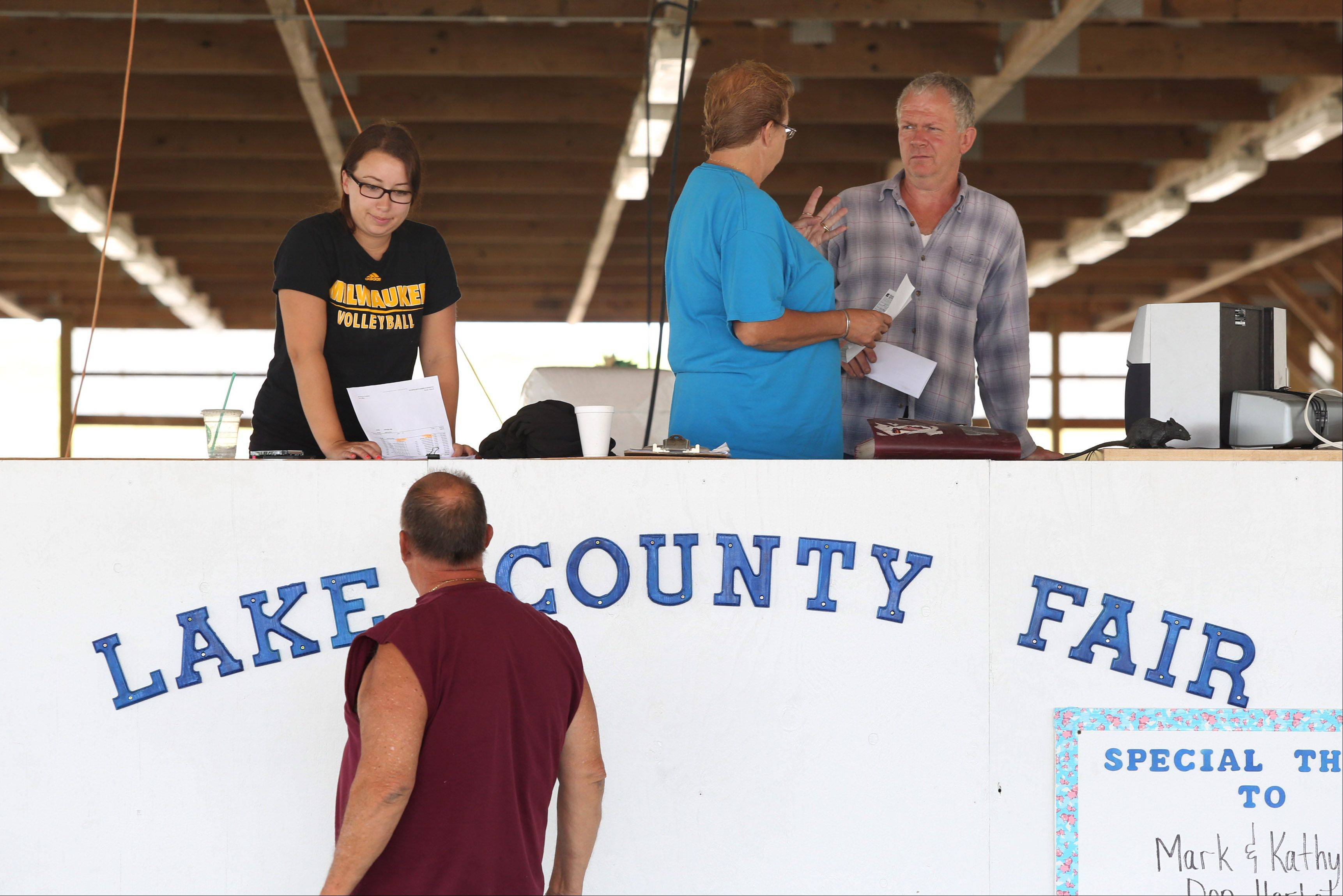 Volunteer Kelsey Quinn, left, and barn superintendant Barb Pretzman talk to Jim Lallaman Tuesday at the Lake County Fair in Grayslake.