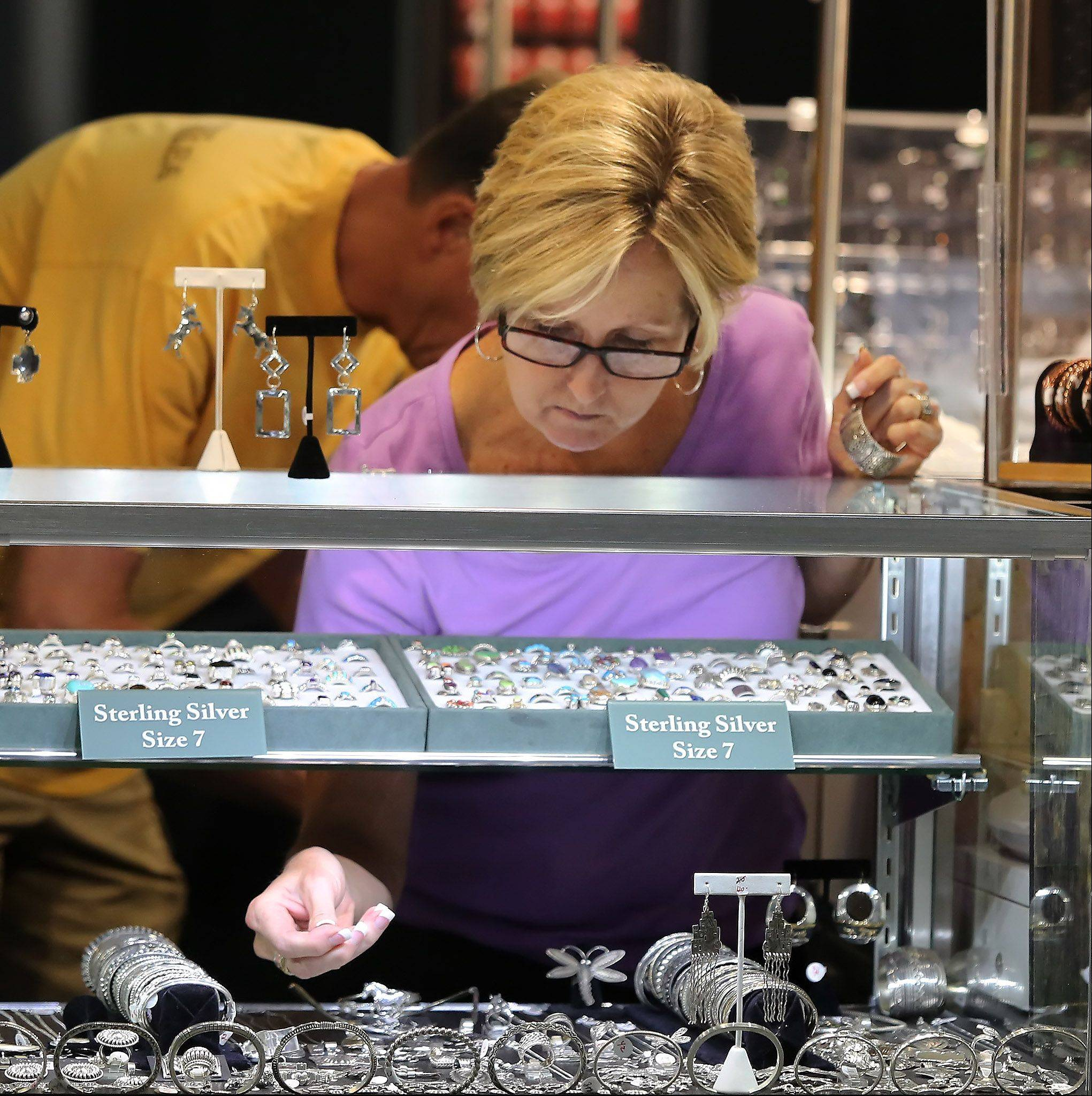 Teri Matzdorf of The Silver Gallery arranges jewelry in the showcases Tuesday in preparing for the start of the Lake County Fair in Grayslake.