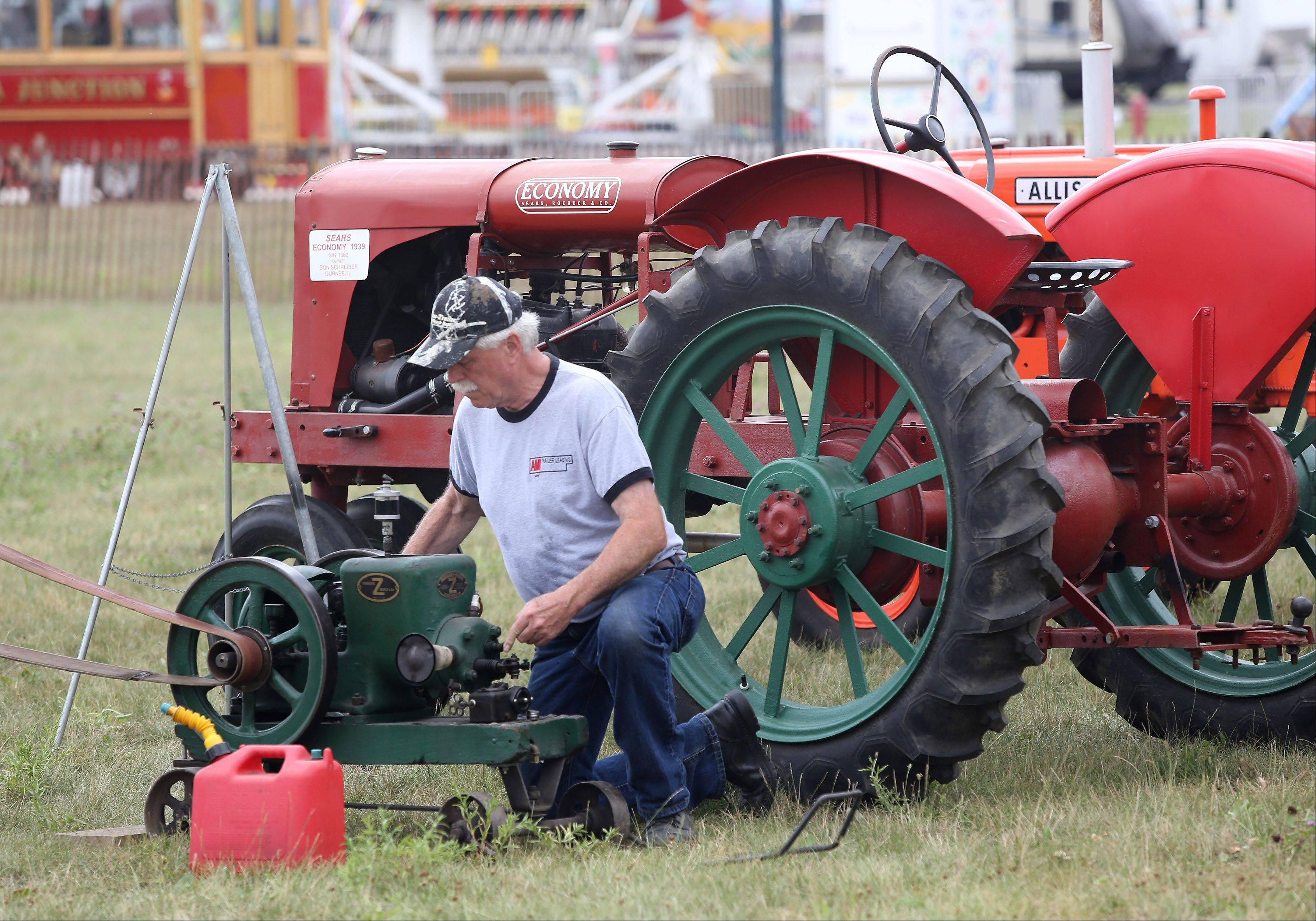 Farm show coordinator Don Schreiber of Gurnee works in the Lake County Farm Heritage Association, Inc. exhibit Tuesday in preparation for Wednesday's start of the Lake County Fair in Grayslake.