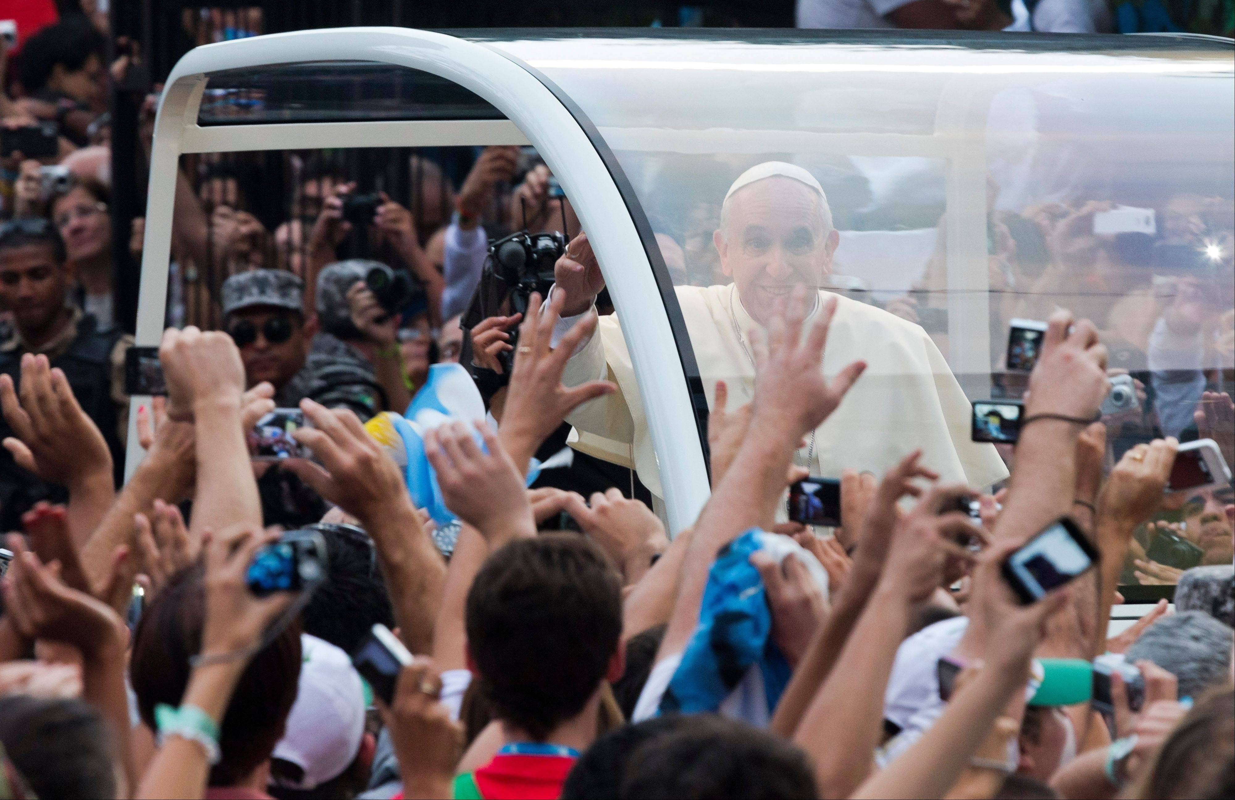 People reach out to Pope Francis as he rides in a popemobile through Rio de Janeiro, Brazil, Monday, July 22, 2013. Pope Francis returned to his home continent for the first time as pontiff, embarking on a visit meant to fan the fervor of the faithful around the globe.