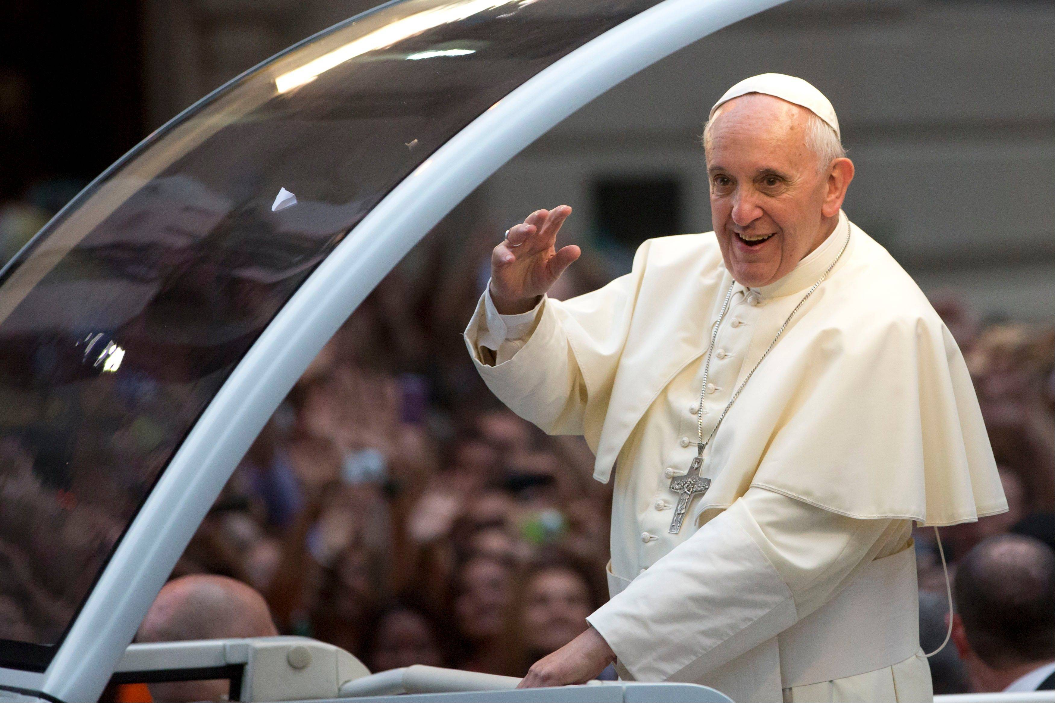 Pope Francis waves from his popemobile as he makes his way into central Rio de Janeiro,
