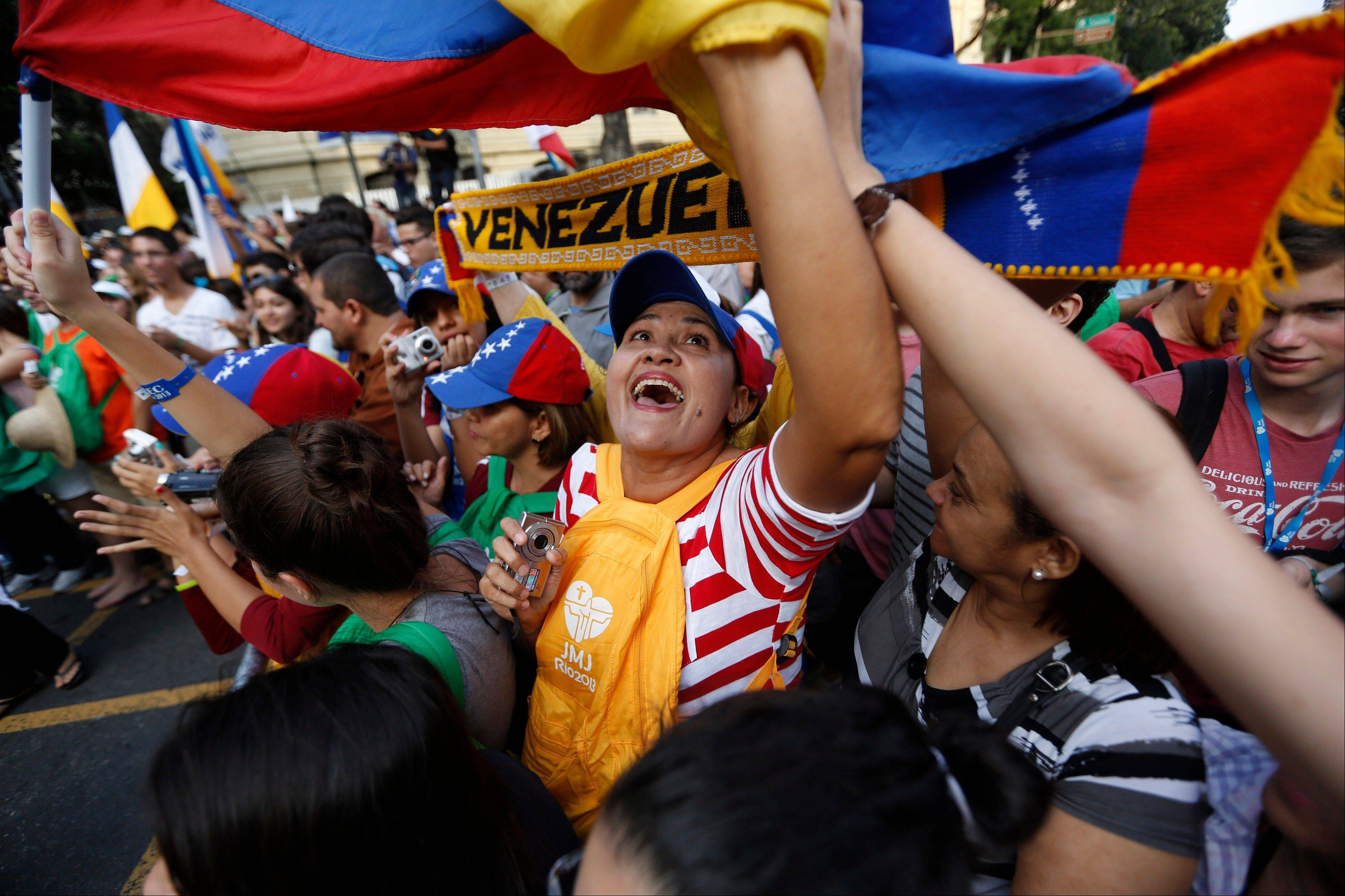 A Venezuelan waves her country's flag as she waits for the arrival of Pope Francis in Rio de Janeiro, Brazil, Monday, July 22, 2013. Frenzied crowds of Roman Catholics lined the streets to see Francis on Monday.